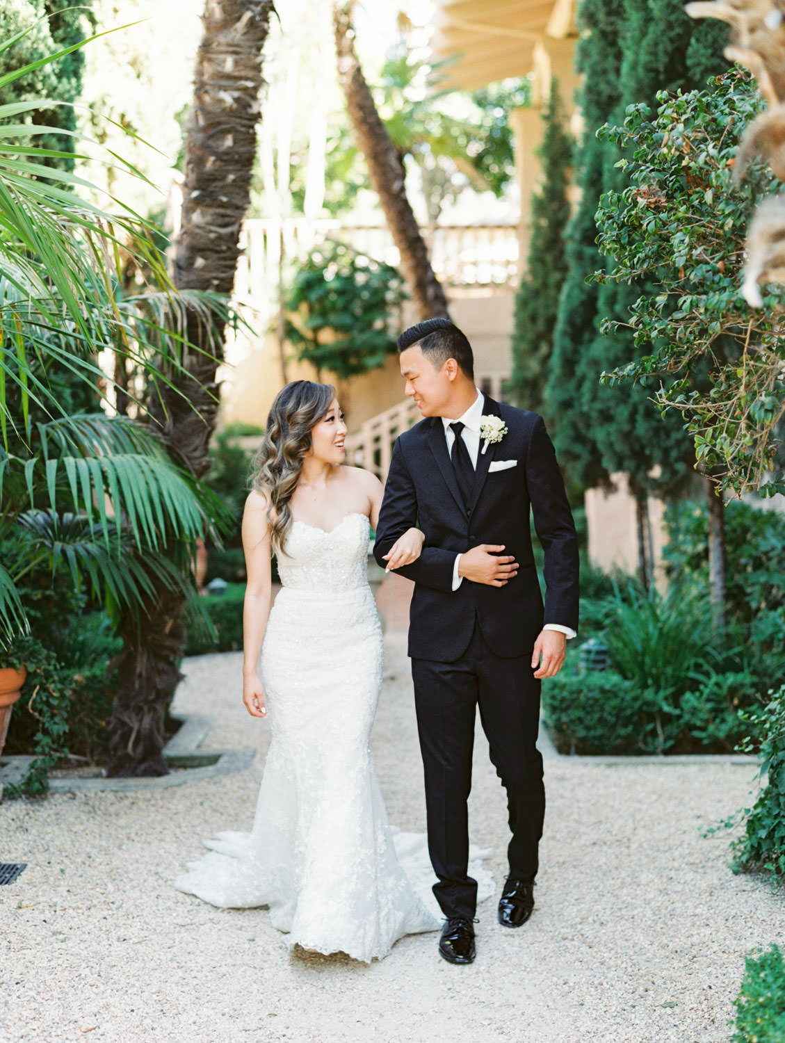 Bride and groom portrait in front of cyprus tree grove. Groom in a three piece black tuxedo and bride in a Martina Liana gown. Wedding at Rancho Bernardo Inn. Film photo by Cavin Elizabeth Photography