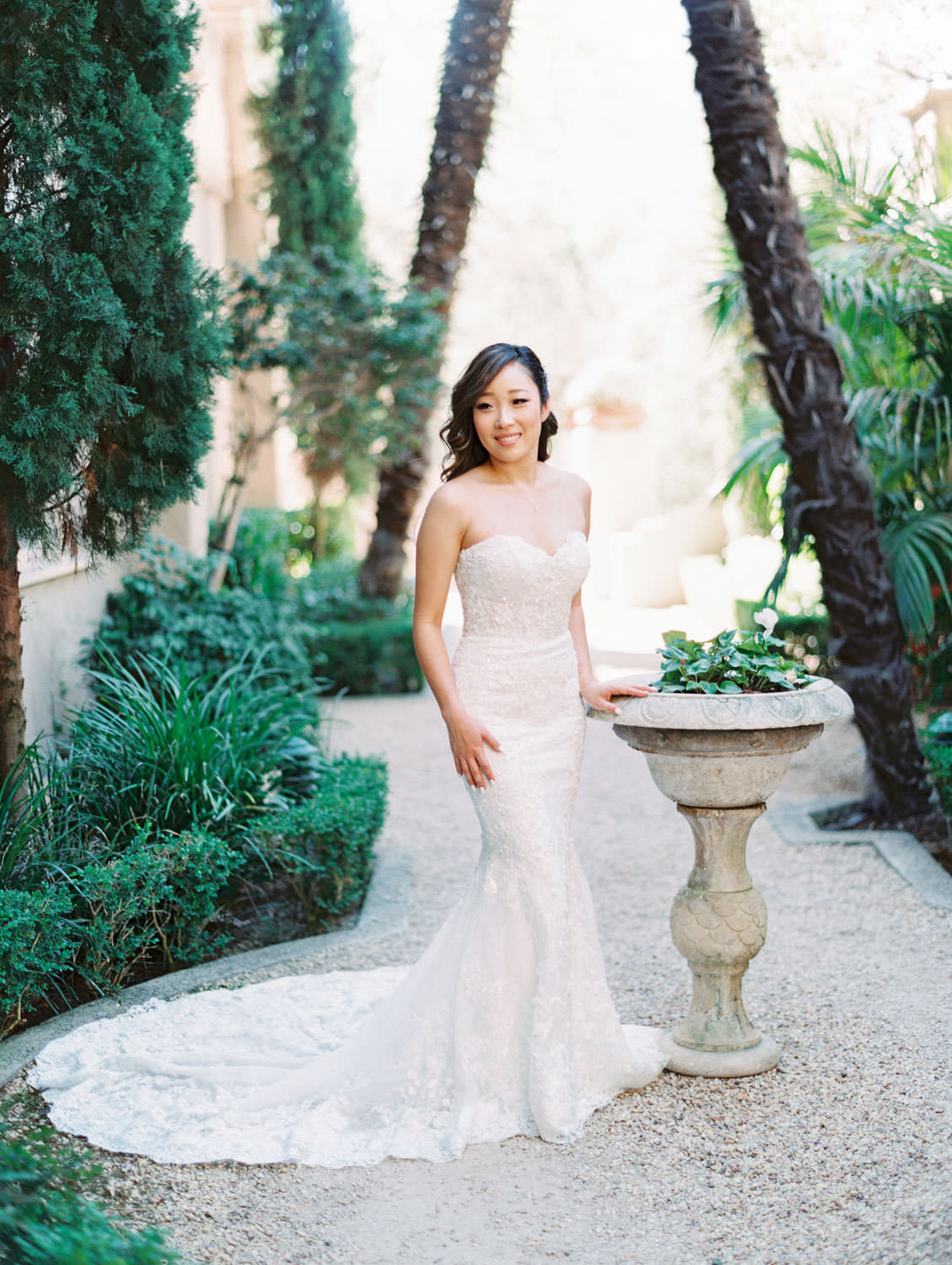 Bridal portrait in front of cyprus tree grove and fountain. Bride in a Martina Liana gown from the White Flower Bridal Boutique. Rancho Bernardo Inn wedding. Film photo by Cavin Elizabeth Photography