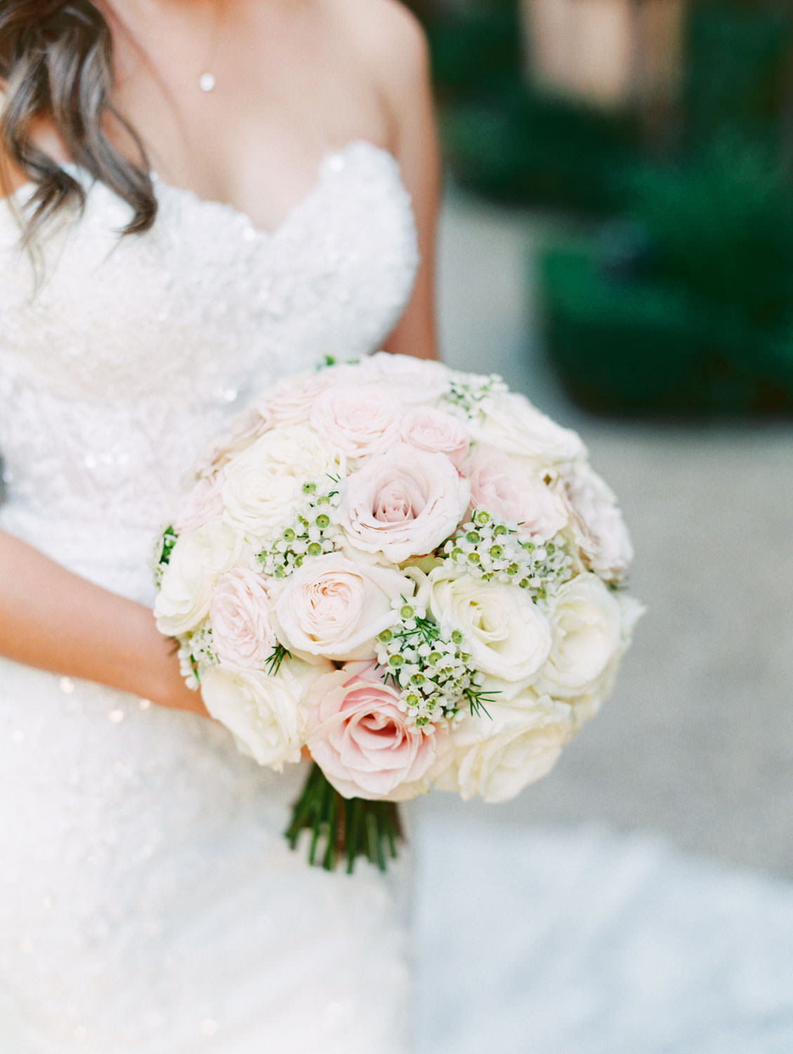 Round pave bouquet with ivory and blush roses and greenery. Bride in a Martina Liana gown from the White Flower Bridal Boutique. Rancho Bernardo Inn wedding. Film photo by Cavin Elizabeth Photography