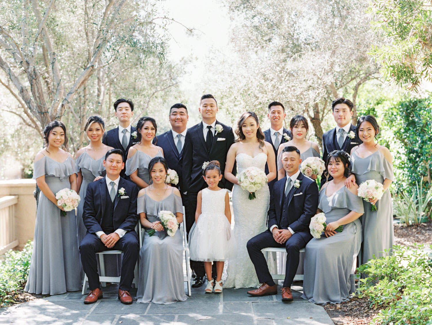 Bridal party portrait with groom in black tux and groomsmen in navy suits. Bridesmaids in grey cut out sleeve gowns. Bride in a Martina Liana gown from the White Flower Bridal Boutique. Rancho Bernardo Inn wedding. Film photo by Cavin Elizabeth Photography