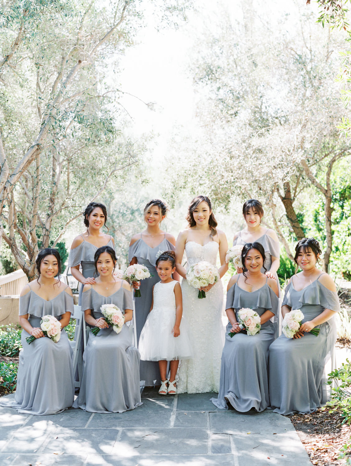 Bridal party portrait with bridesmaids in grey cut out sleeve gowns. Bride in a Martina Liana gown from the White Flower Bridal Boutique. Rancho Bernardo Inn wedding. Film photo by Cavin Elizabeth Photography
