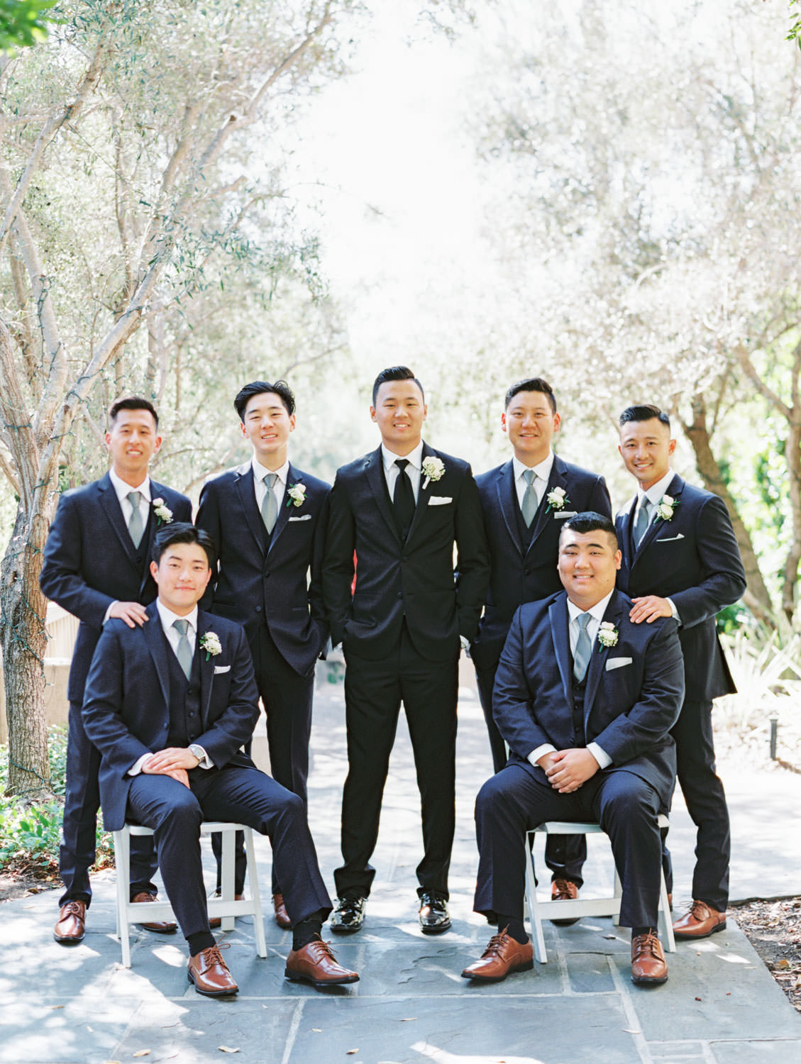 Bridal party portrait with groom in black tux and groomsmen in navy suits. Rancho Bernardo Inn wedding. Film photo by Cavin Elizabeth Photography