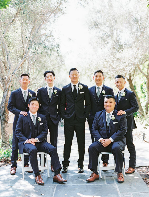 Bridal party portrait with groom in black tux and groomsmen in navy suits. Rancho Bernardo Inn wedding. Film photo by Cavin Elizabeth Photography