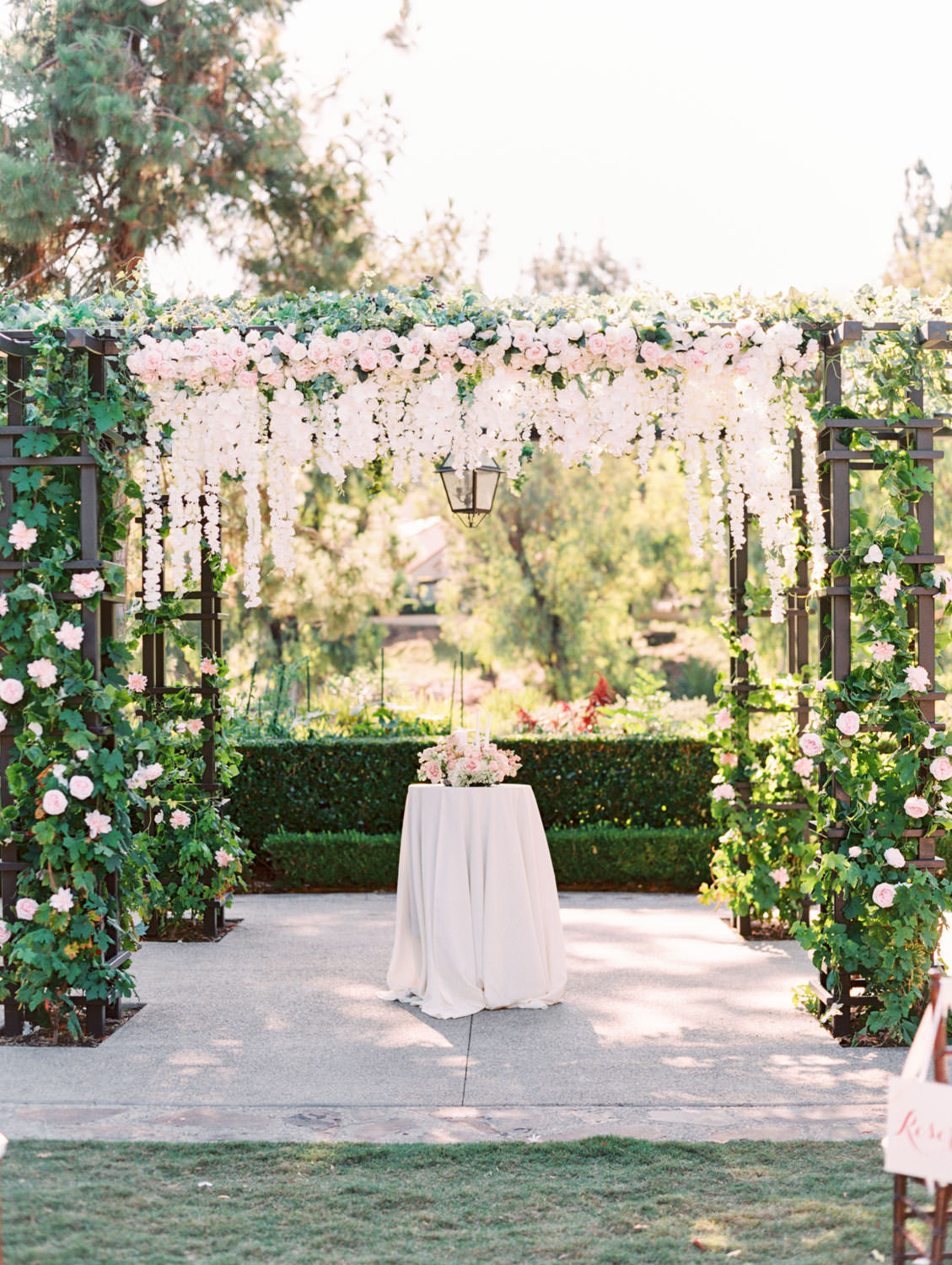 Pergola wrapped in greenery with blush flowers on the side columns and hanging blush and ivory flowers in the center. Rancho Bernardo Inn Aragon lawn wedding ceremony. Film photo by Cavin Elizabeth Photography