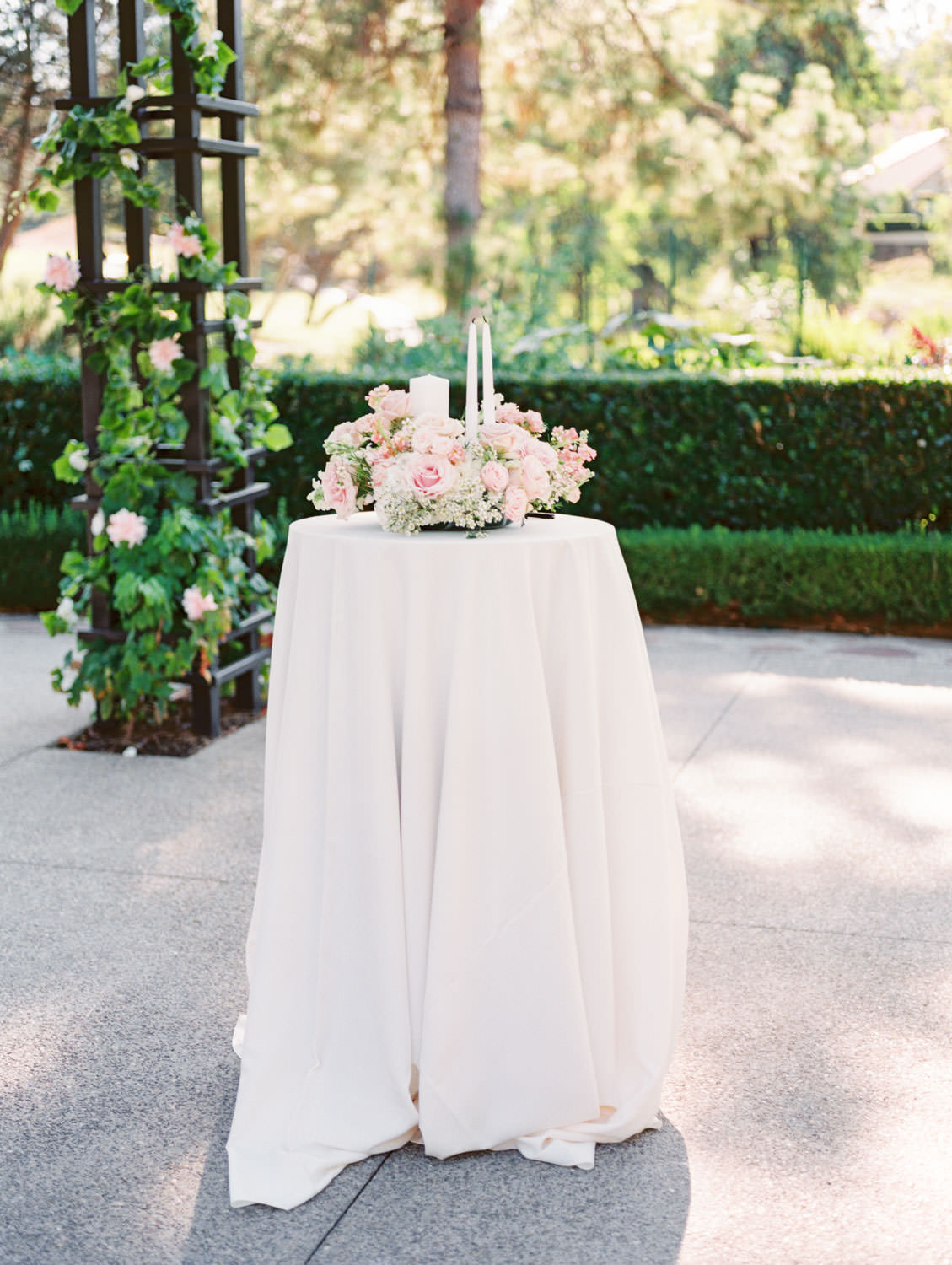Candle lighting table topped with blush and ivory flowers and ivory candles. Rancho Bernardo Inn Aragon lawn wedding ceremony. Film photo by Cavin Elizabeth Photography