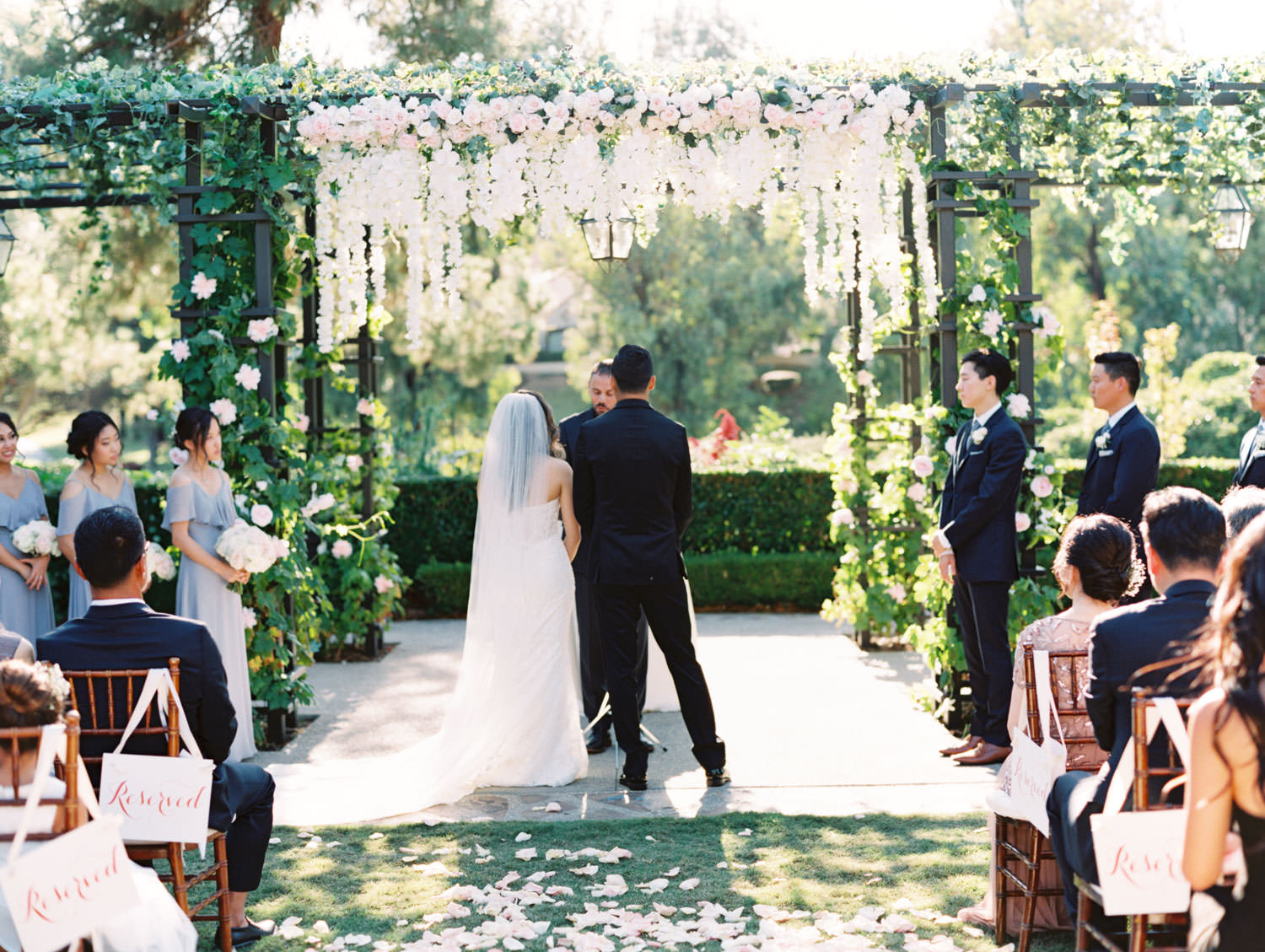Bride and groom in front of Pergola wrapped in greenery with blush flowers on the side columns and hanging blush and ivory flowers in the center. Rancho Bernardo Inn Aragon lawn wedding ceremony. Film photo by Cavin Elizabeth Photography