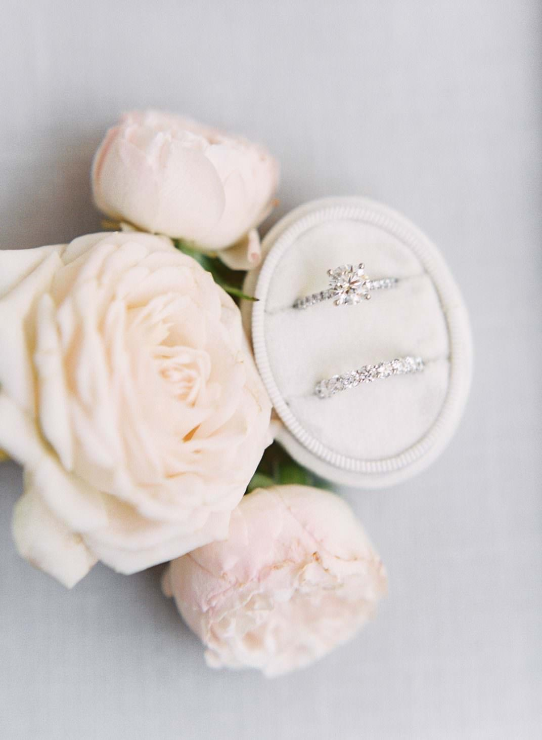 Brides diamond ring with pave band and matching wedding band in an oval ivory velvet ring box styled with blush roses. Wedding at Rancho Bernardo Inn. Film photo by Cavin Elizabeth Photography