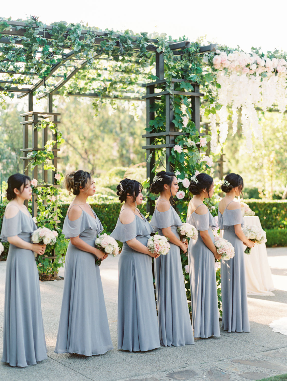 Bridesmaids in soft grey cut out shoulder gowns. Pergola wrapped in greenery with blush flowers on the side columns and hanging blush and ivory flowers in the center. Rancho Bernardo Inn Aragon lawn wedding ceremony. Film photo by Cavin Elizabeth Photography