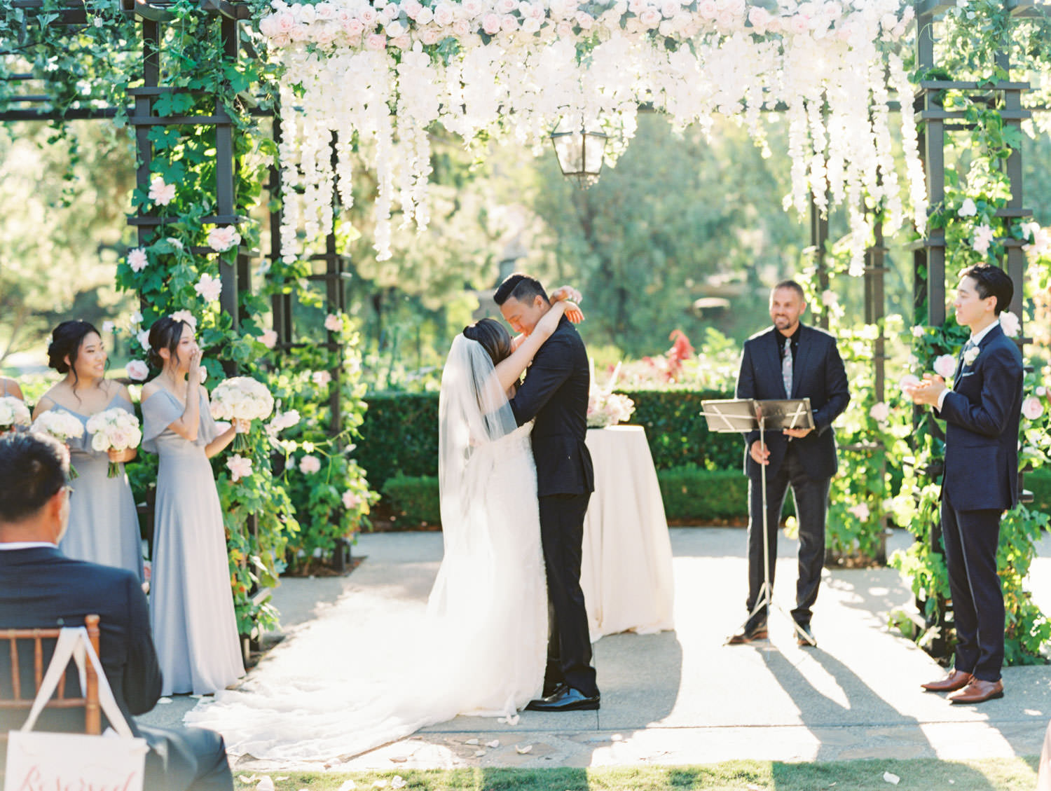 Bride and groom first kiss in front of a Pergola wrapped in greenery with blush flowers on the side columns and hanging blush and ivory flowers in the center. Rancho Bernardo Inn Aragon lawn wedding ceremony. Film photo by Cavin Elizabeth Photography