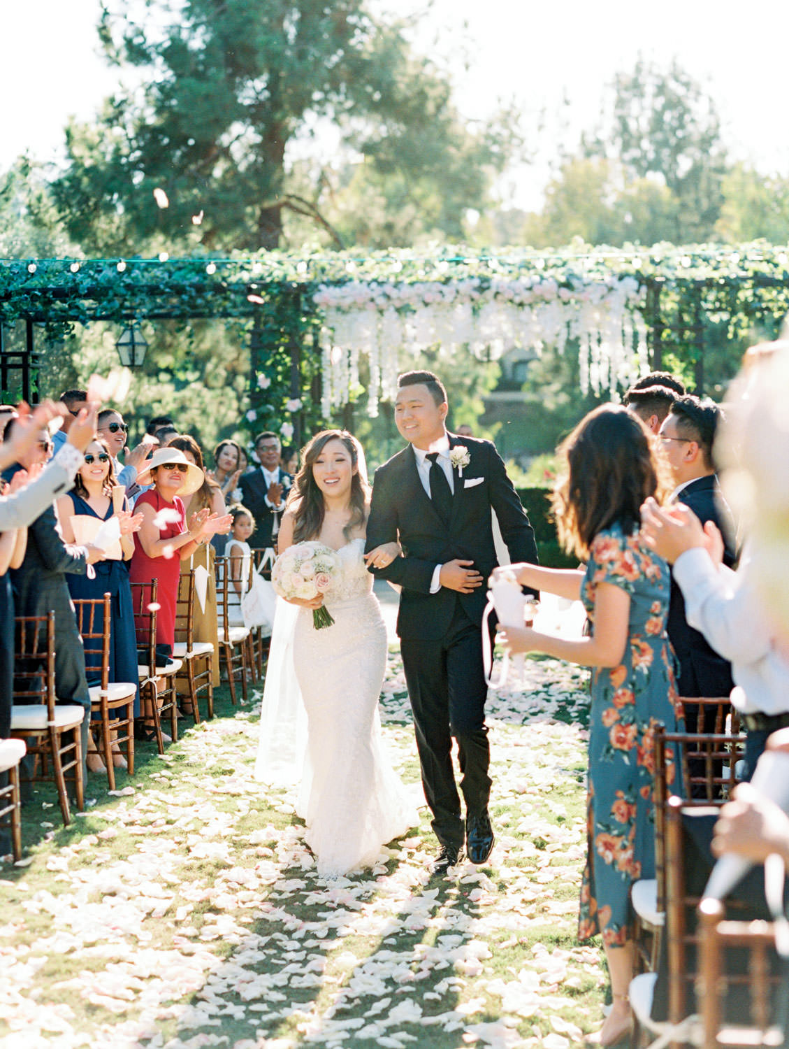 Bride and groom walking down the aisle with flowers thrown in the air in front of a Pergola wrapped in greenery with blush flowers on the side columns and hanging blush and ivory flowers in the center. Rancho Bernardo Inn Aragon lawn wedding ceremony. Film photo by Cavin Elizabeth Photography