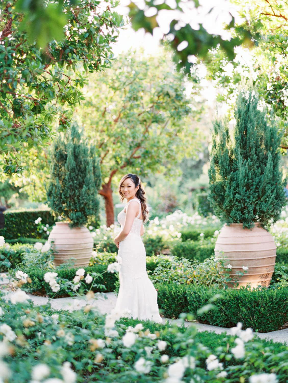 Bride in a rose garden in a Martina Liana gown from The White Flower. Rancho Bernardo Inn Aragon lawn wedding. Film photo by Cavin Elizabeth Photography