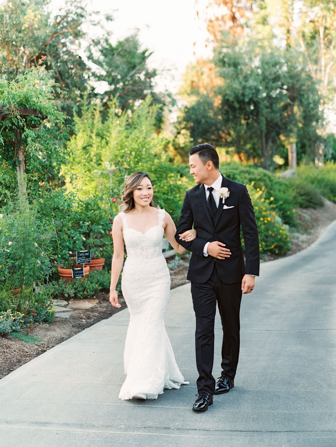 Groom in black tux and bride walking through a garden in a Martina Liana gown from The White Flower. Wedding at Rancho Bernardo Inn. Film photo by Cavin Elizabeth Photography