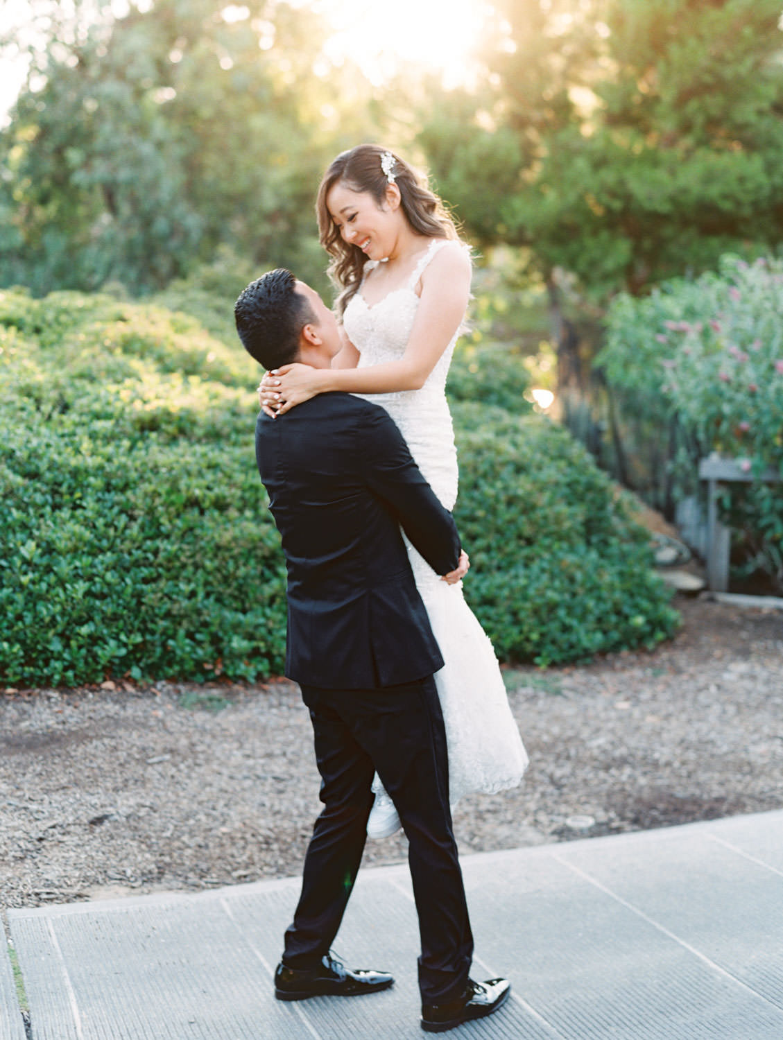 Groom in black tux and bride in a rose garden in a Martina Liana gown from The White Flower. Wedding at Rancho Bernardo Inn. Film photo by Cavin Elizabeth Photography