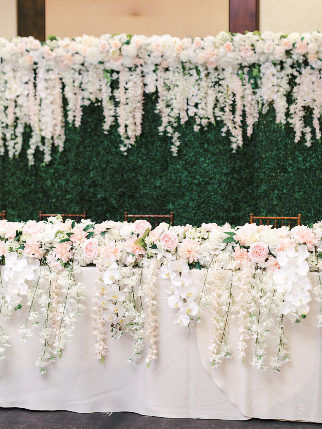 Head table on a stage with a greenery wall backdrop with hanging white and pink flowers on the wall and on the table. Wedding at Rancho Bernardo Inn in the Aragon Ballroom. photo by Cavin Elizabeth Photography