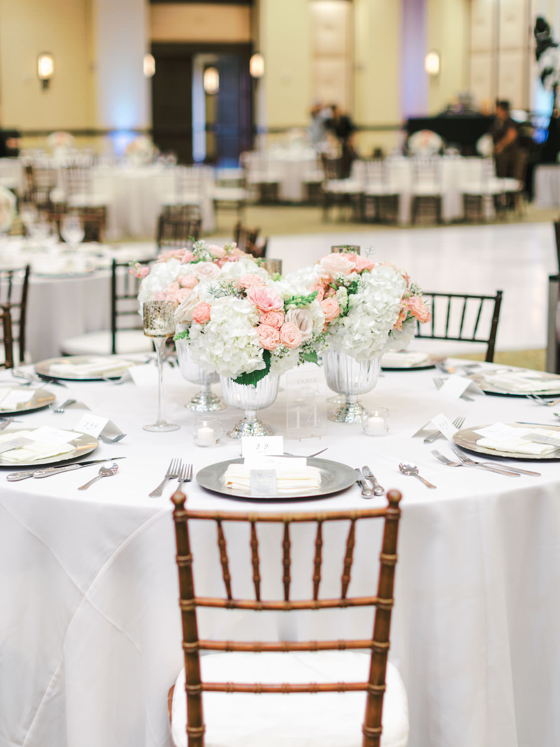 Reception with white linens, oak Chiavari chairs, and ivory, blush, and green centerpieces. Wedding at Rancho Bernardo Inn in the Aragon Ballroom. photo by Cavin Elizabeth Photography