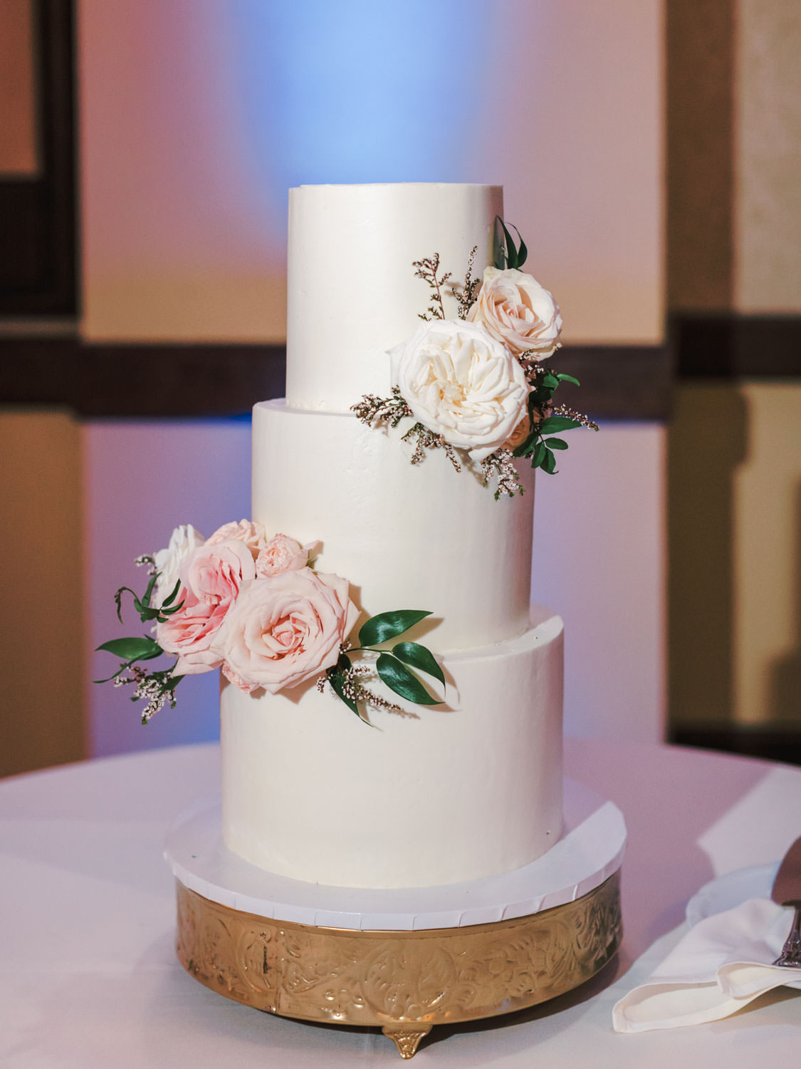 Wedding cake with three white tiers and ivory and pink roses with pops of greenery. photo by Cavin Elizabeth Photography
