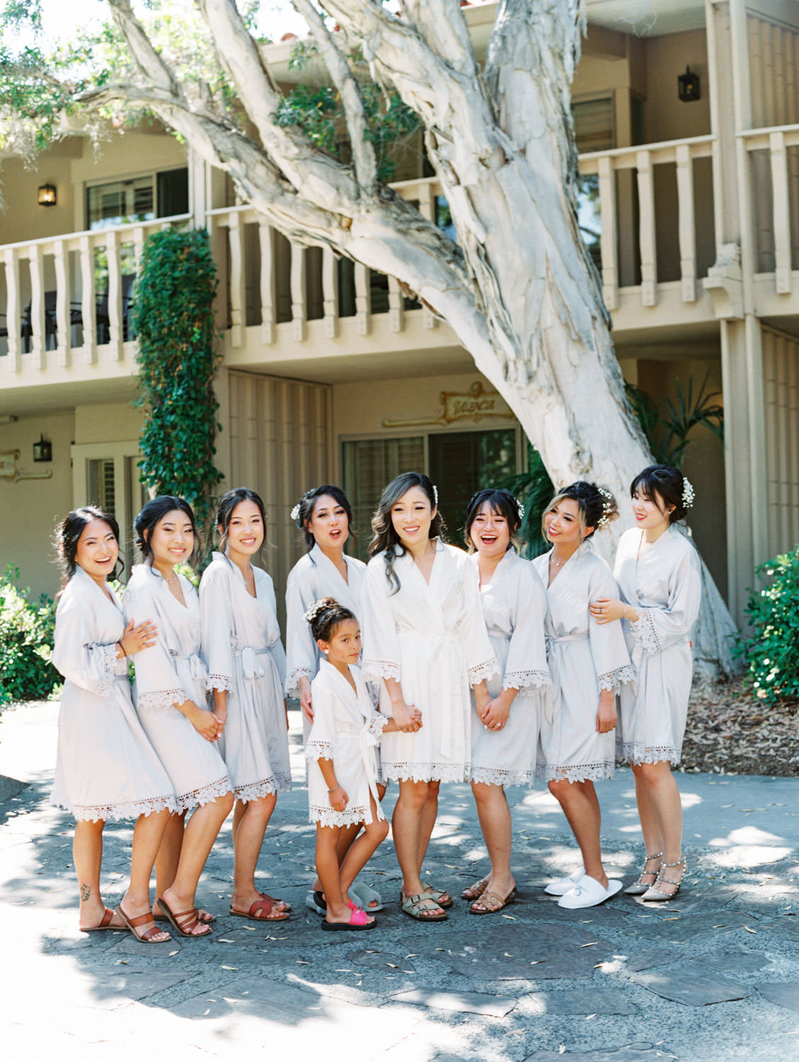 Bride in a white robe and bridesmaids in soft grey robes getting ready. Wedding at Rancho Bernardo Inn. Film photo by Cavin Elizabeth Photography