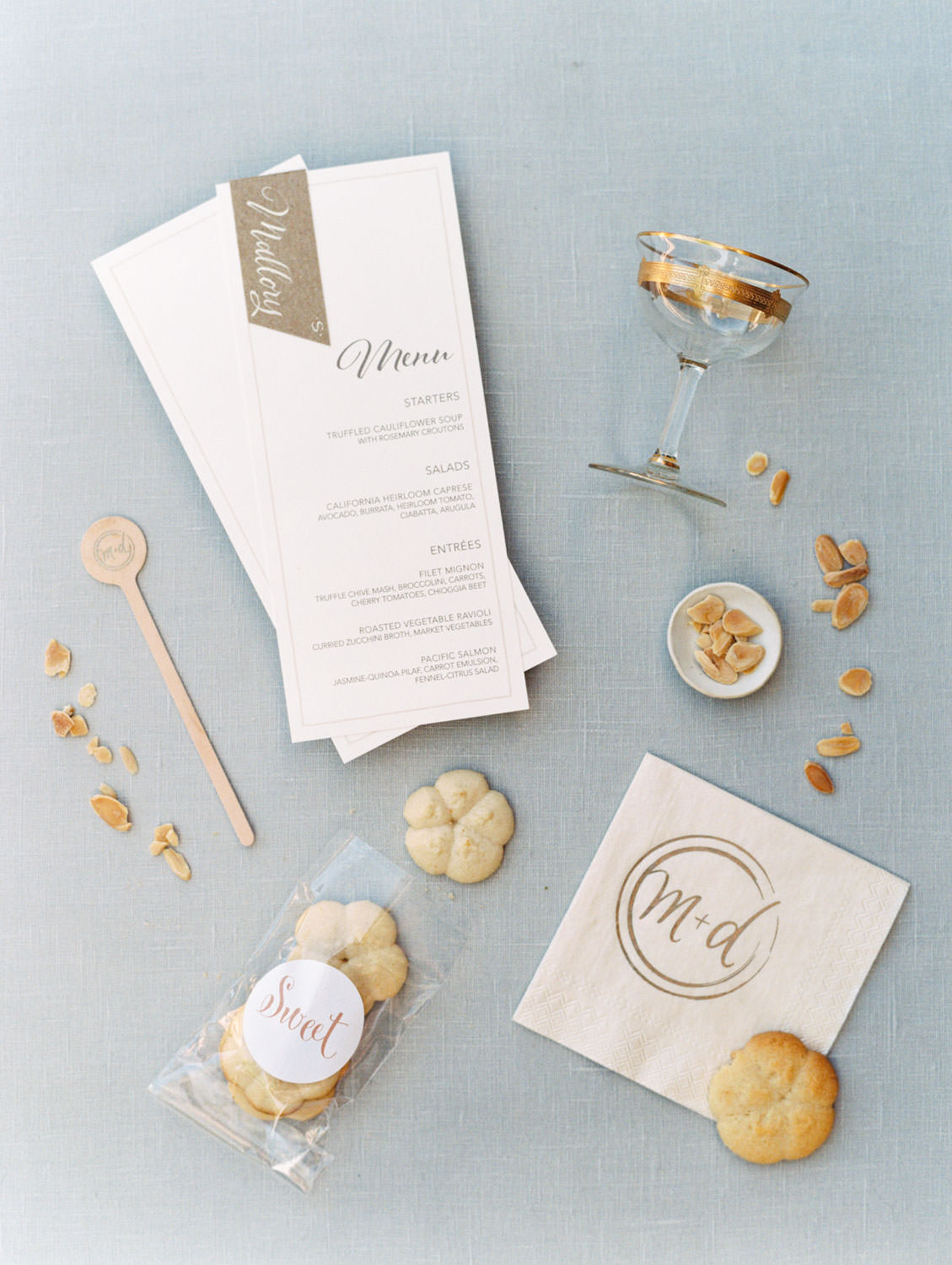 Ivory menu styled with wedding cookies, stir sticks, and custom initial napkins. Estancia La Jolla wedding shot on film by Cavin Elizabeth Photography