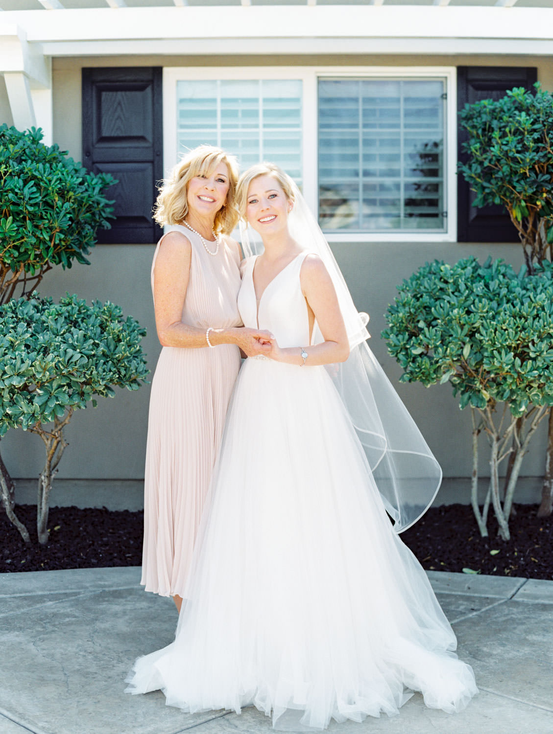 Bride in Stella York gown and veil with her mother in a blush cocktail dress. Estancia La Jolla wedding shot on film by Cavin Elizabeth Photography. San Diego wedding shot on film by Cavin Elizabeth Photography