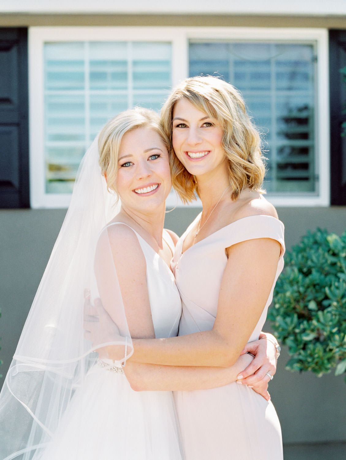 Bride in Stella York gown and veil for a classic bridal portrait with her sister in a blush off shoulder gown. San Diego wedding shot on film by Cavin Elizabeth Photography