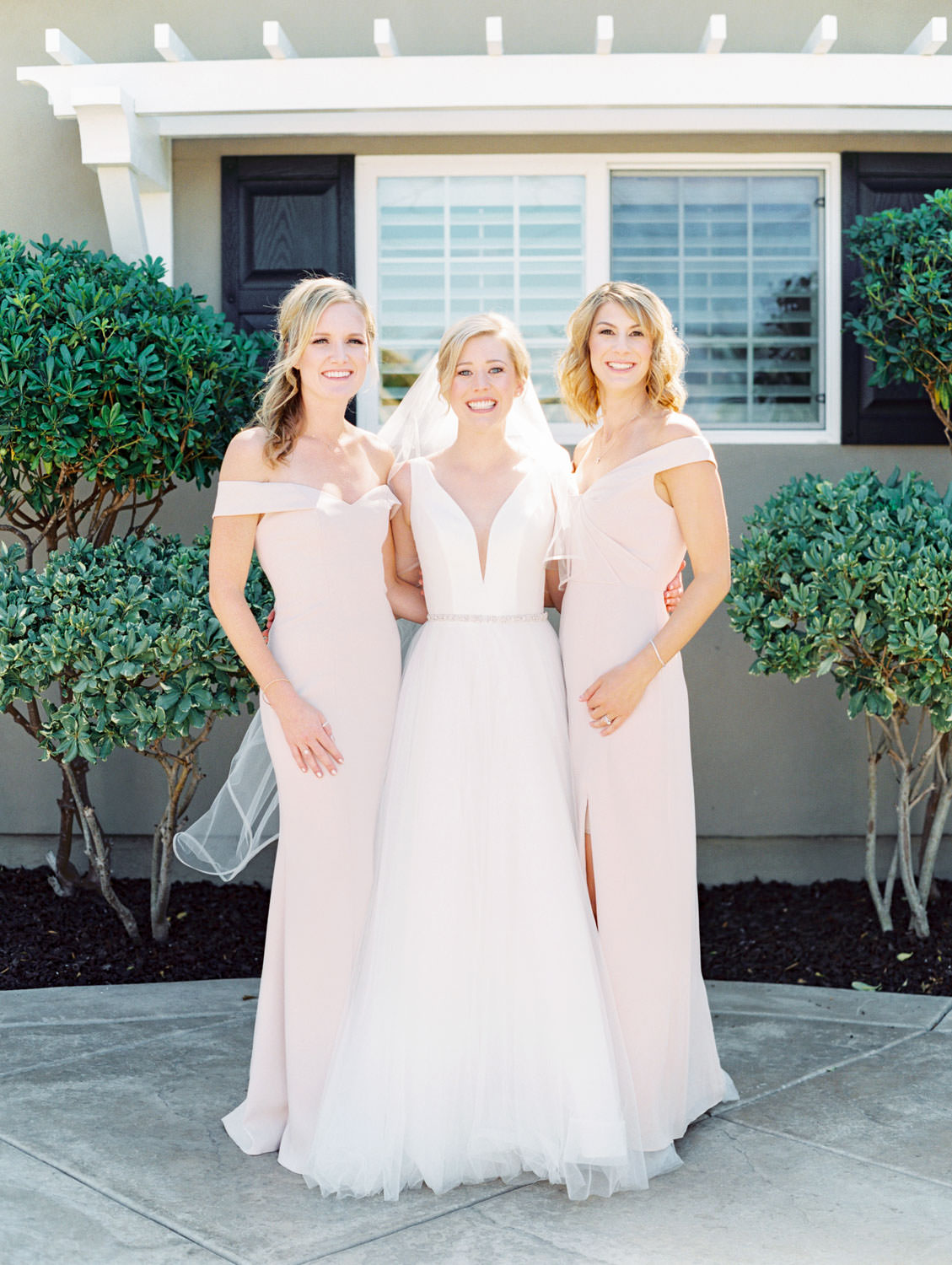 Bride in Stella York gown and veil for a classic bridal portrait with her bridesmaids in blush off shoulder gowns. San Diego wedding shot on film by Cavin Elizabeth Photography