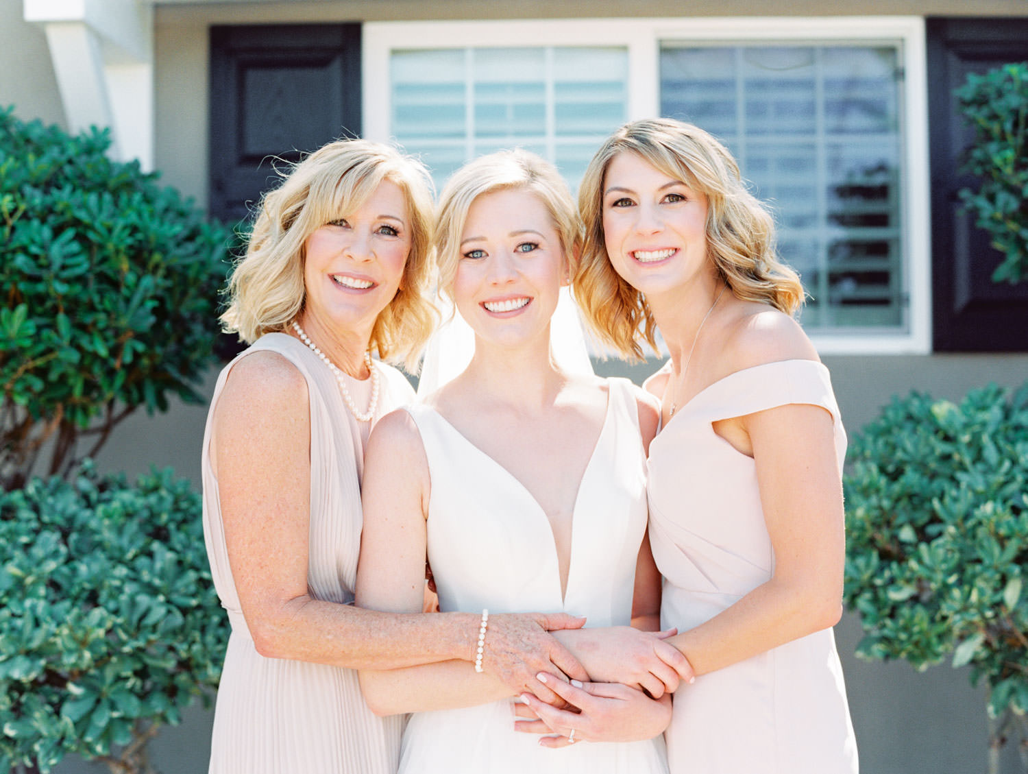 Bride in Stella York gown and veil for a classic bridal portrait with her mom and sister in blush gowns. San Diego wedding shot on film by Cavin Elizabeth Photography