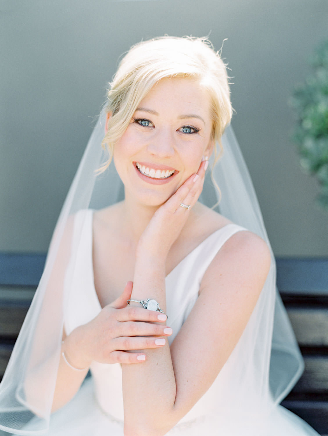 Bride in Stella York gown and veil for a classic bridal portrait. Bridal updo with hair loose and curled in front. San Diego wedding shot on film by Cavin Elizabeth Photography