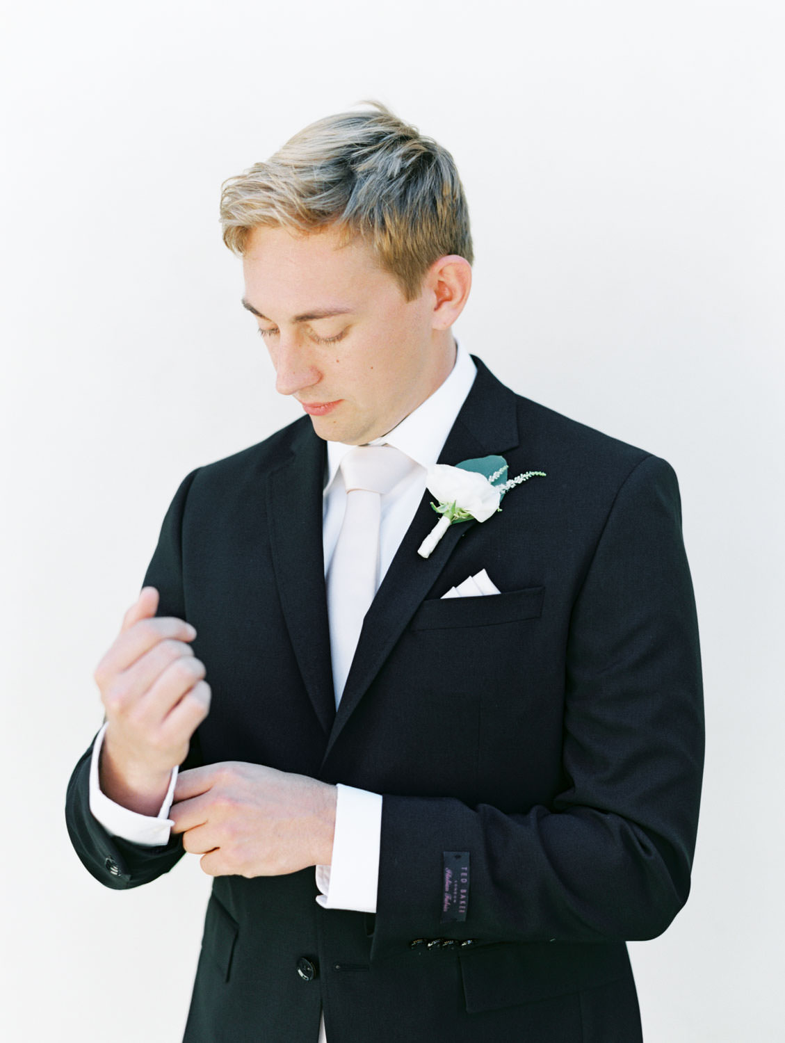 Groom in black suit with pale blush tie and ivory rose boutonniere with eucalyptus leaf. Estancia La Jolla wedding shot on film by Cavin Elizabeth Photography. La Jolla wedding shot on film by Cavin Elizabeth Photography