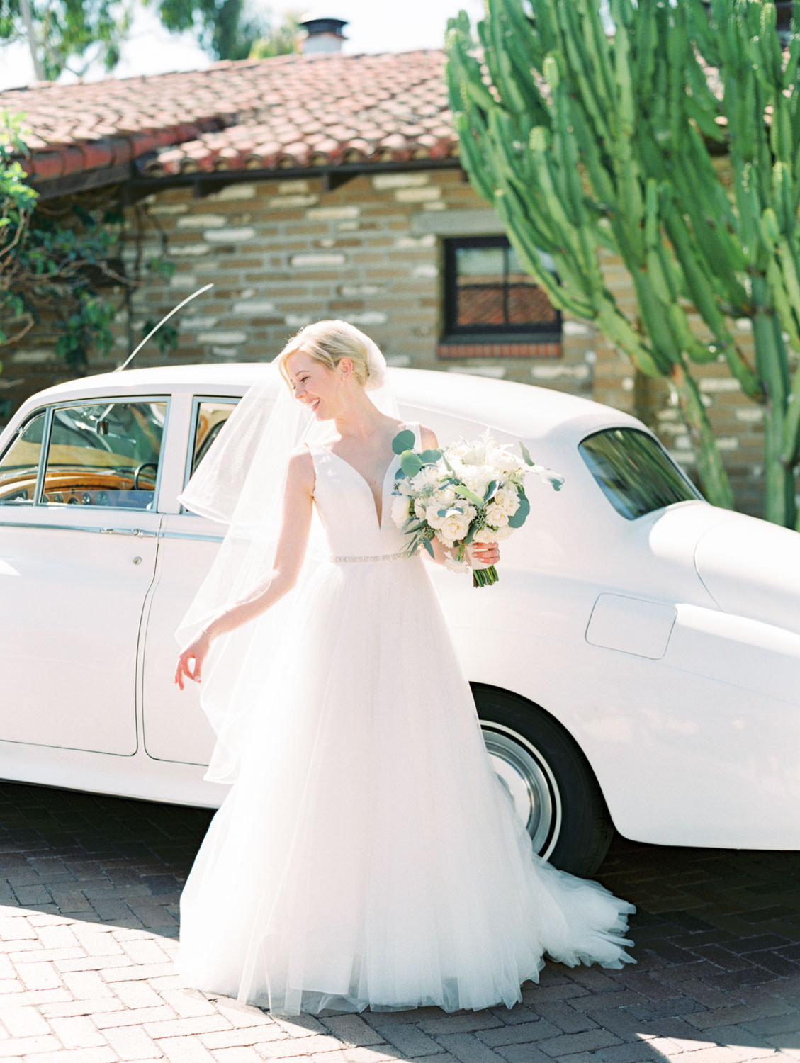 Bride in white vintage Rolls Royce with dahlia and rose ivory bouquet with silver dollar eucalyptus. La Jolla wedding shot on film by Cavin Elizabeth Photography