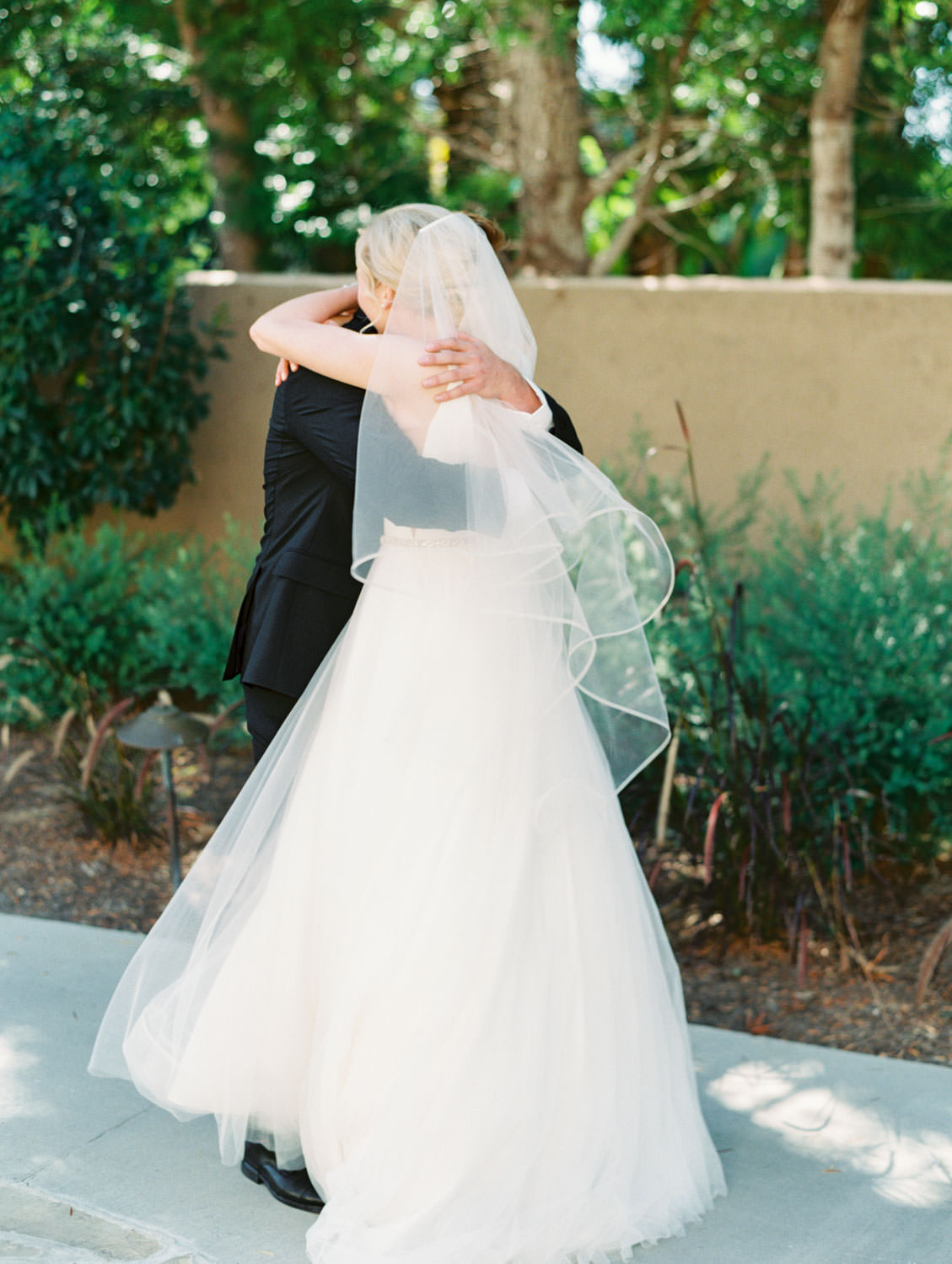 Bride and groom cute first look photo of them tightly hugging. La Jolla wedding shot on film by Cavin Elizabeth Photography