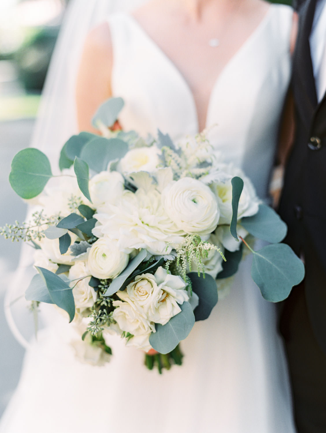 Groom in black suit and blush tie posing with bride in Stella York gown with dahlia and rose ivory bouquet with silver dollar eucalyptus. La Jolla wedding shot on film by Cavin Elizabeth Photography