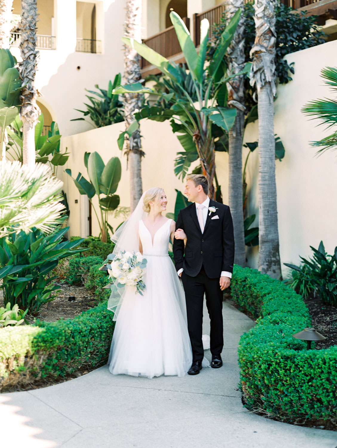 Groom in black suit and blush tie walking with bride in Stella York gown with dahlia and rose ivory bouquet with silver dollar eucalyptus. La Jolla wedding shot on film by Cavin Elizabeth Photography