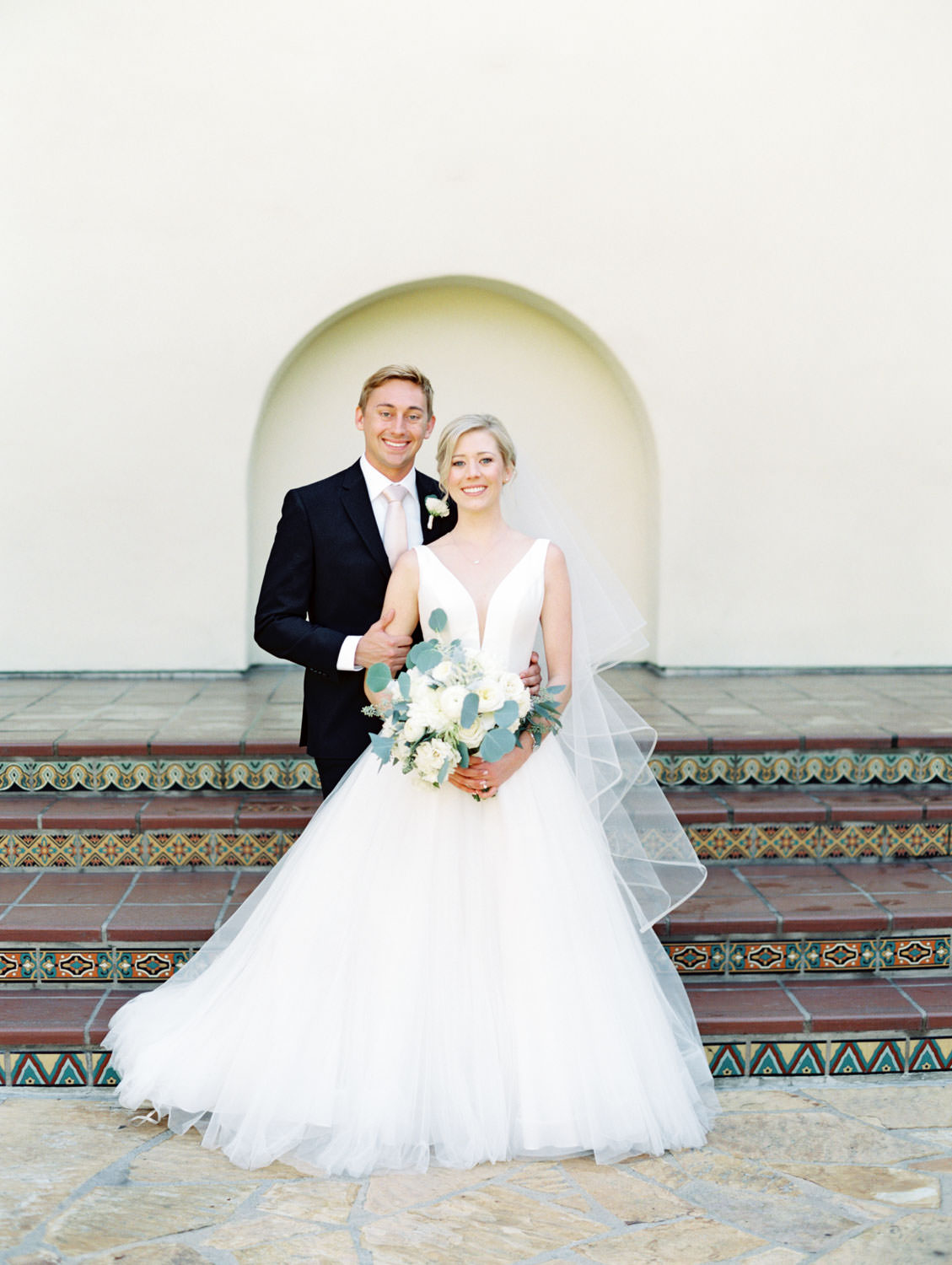 Groom in black suit and blush tie posing in front of white wall with bride in Stella York gown with dahlia and rose ivory bouquet with silver dollar eucalyptus. La Jolla wedding shot on film by Cavin Elizabeth Photography