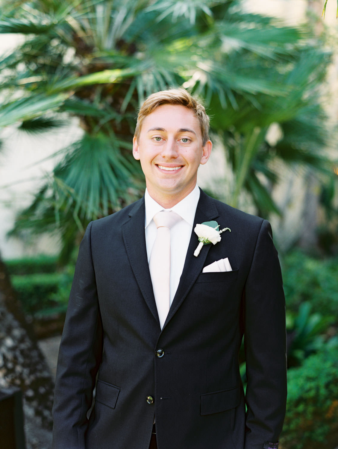 Groom in black suit and blush tie with rose boutonniere. La Jolla wedding shot on film by Cavin Elizabeth Photography