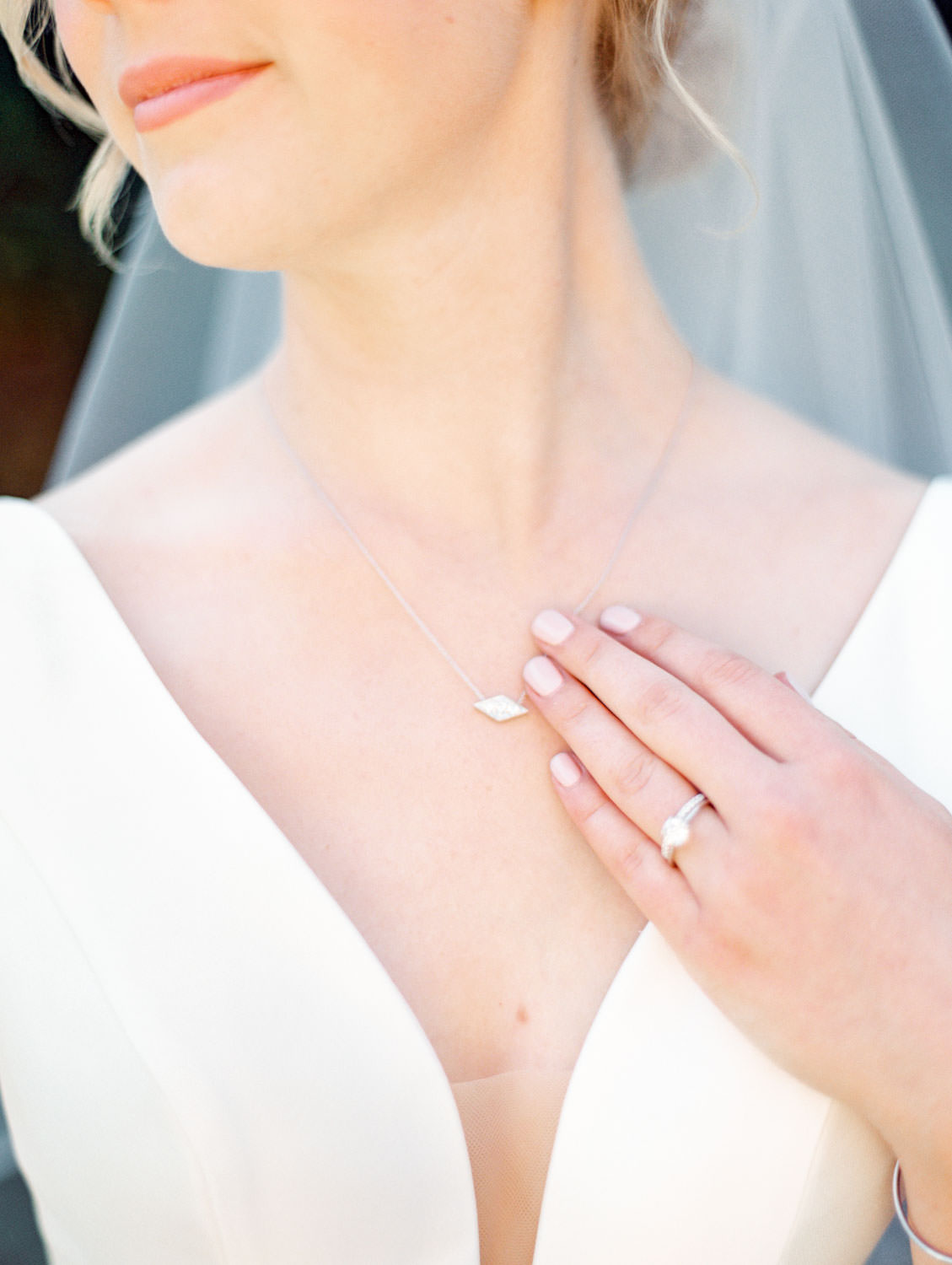 Bride in Stella York gown with blush nails and sideways diamond necklace. La Jolla wedding shot on film by Cavin Elizabeth Photography