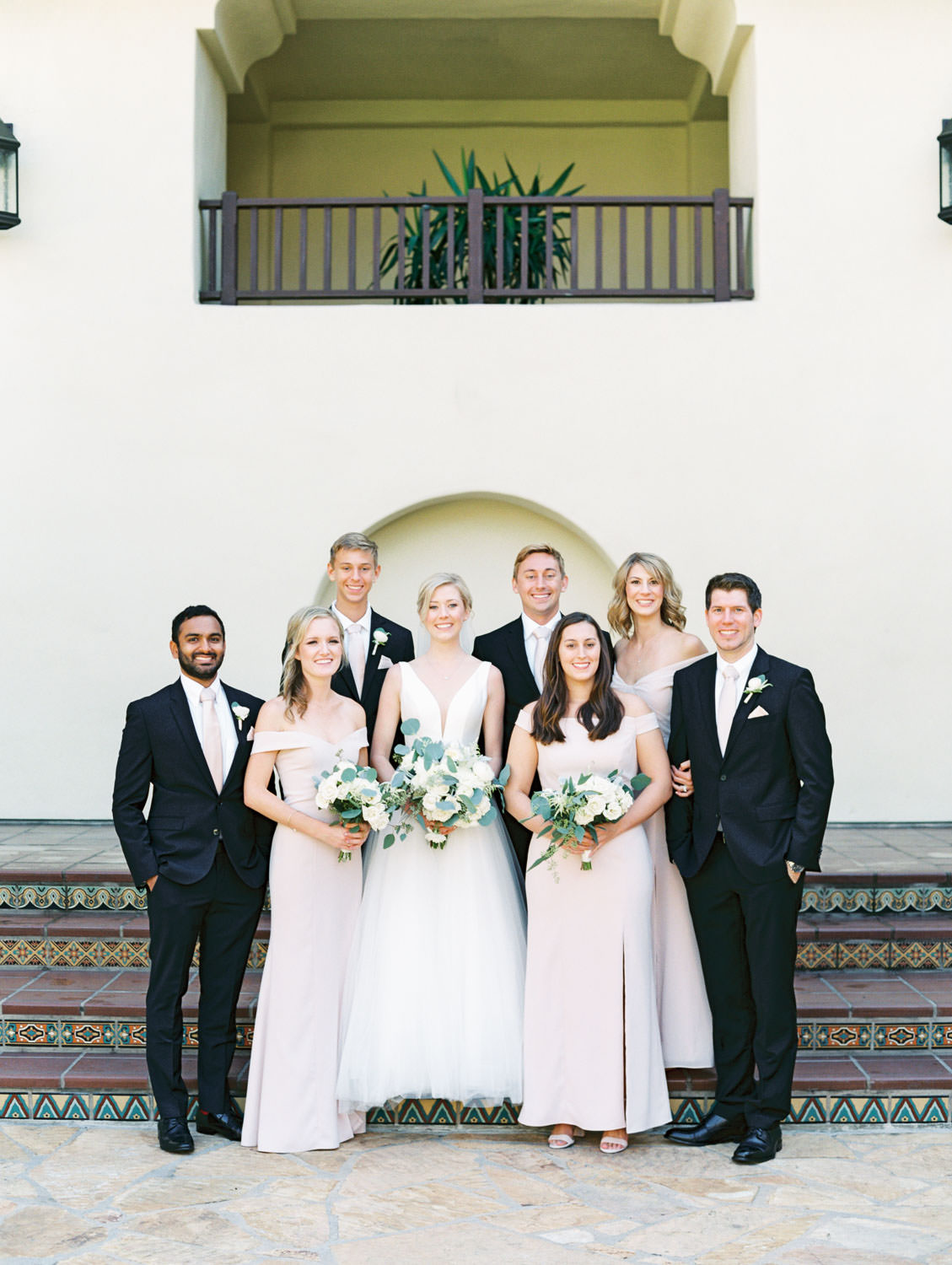 Bridal party portrait with black suits and blush gowns. Groom in black suit and blush tie walking with bride in Stella York gown with dahlia and rose ivory bouquet with silver dollar eucalyptus. La Jolla wedding shot on film by Cavin Elizabeth Photography