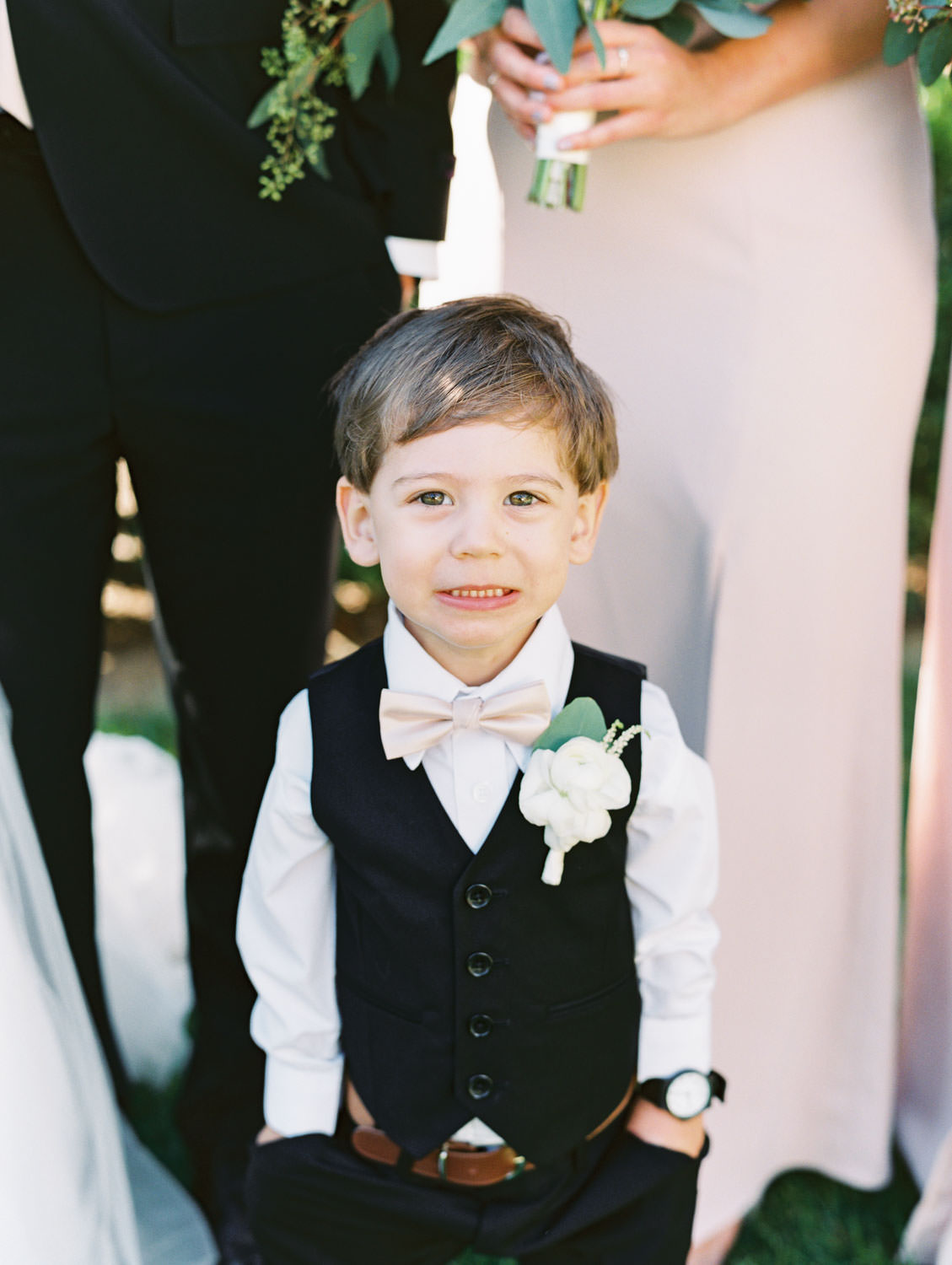 Ring bearer with ranunculus boutonniere and blush bow tie. Estancia La Jolla wedding shot on film by Cavin Elizabeth Photography