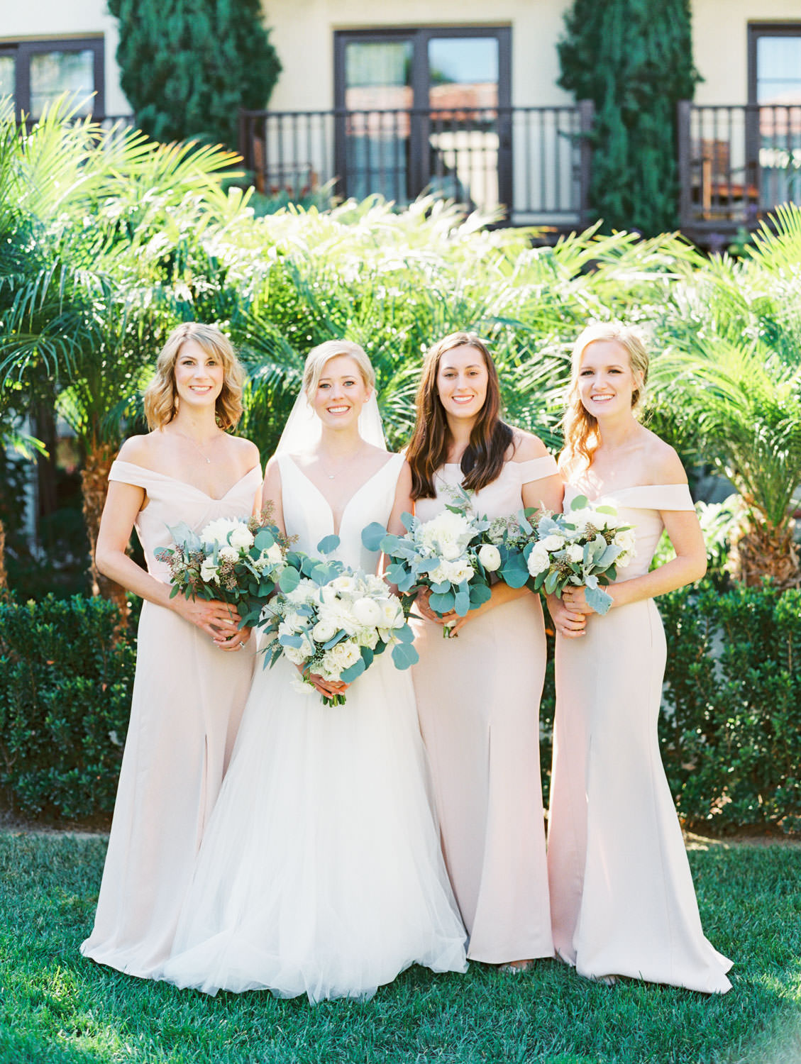 Bridal party portrait with blush gowns. Bride in Stella York gown with dahlia and rose ivory bouquet with silver dollar eucalyptus. La Jolla wedding shot on film by Cavin Elizabeth Photography