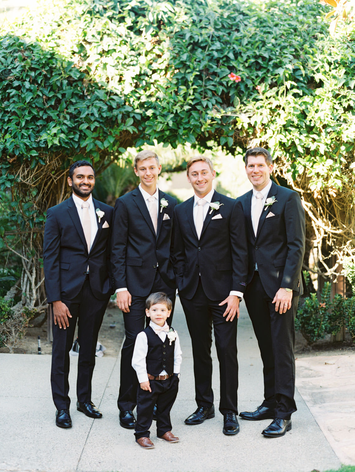 Groom, groomsmen, and ring bearer in black suits and blush ties with eucalyptus and rose boutonnieres. Estancia La Jolla wedding shot on film by Cavin Elizabeth Photography