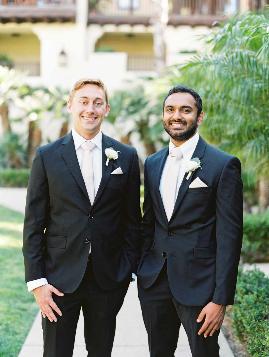 Groom and groomsmen in black suits and blush ties with eucalyptus and rose boutonnieres. Estancia La Jolla wedding shot on film by Cavin Elizabeth Photography