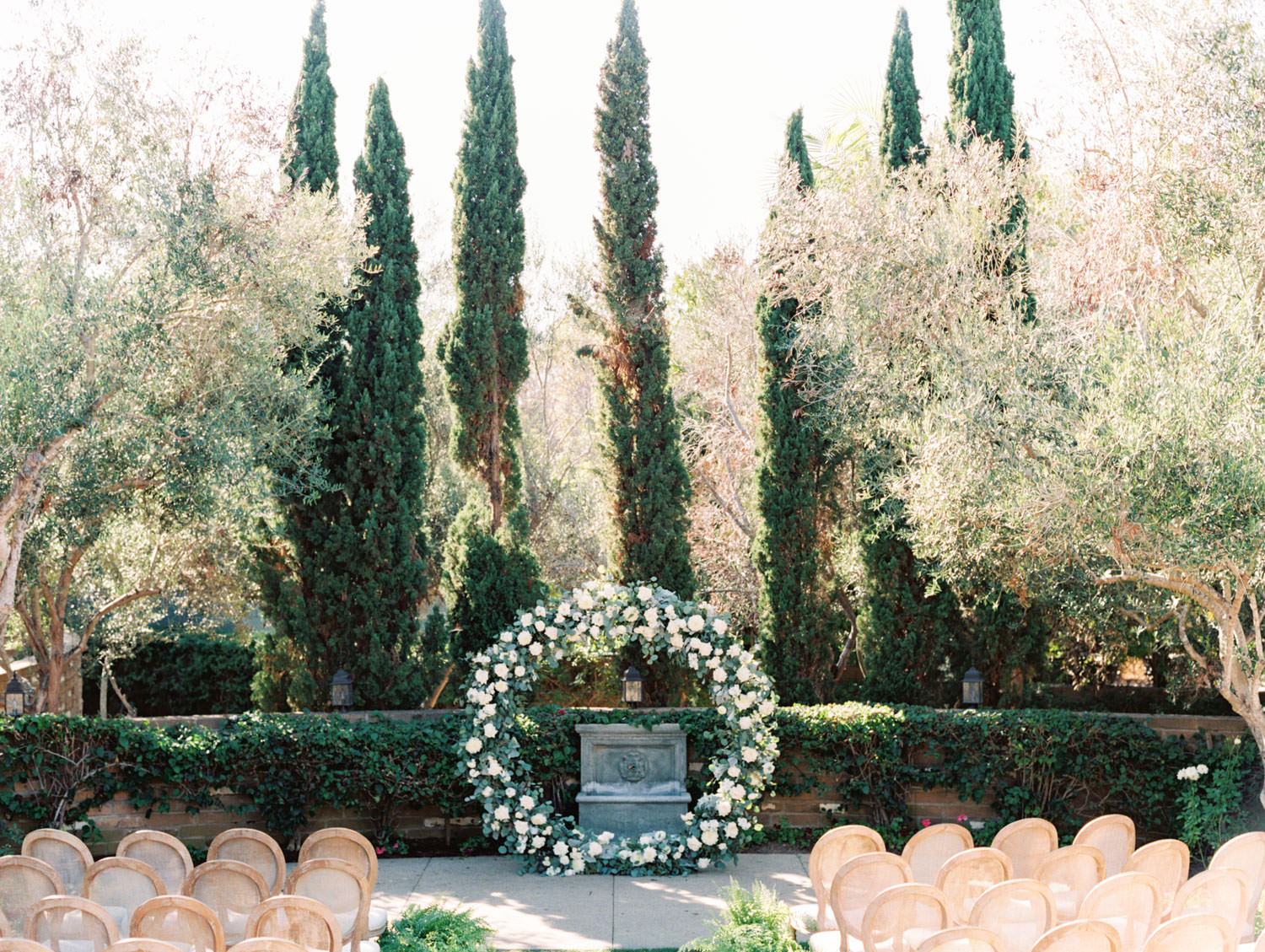 Circular ceremony arch with silver dollar eucalyptus, white dahlias and roses. Olive Lawn ceremony with cane back Louis chairs and ferns along the aisle. Estancia La Jolla wedding shot on film by Cavin Elizabeth Photography
