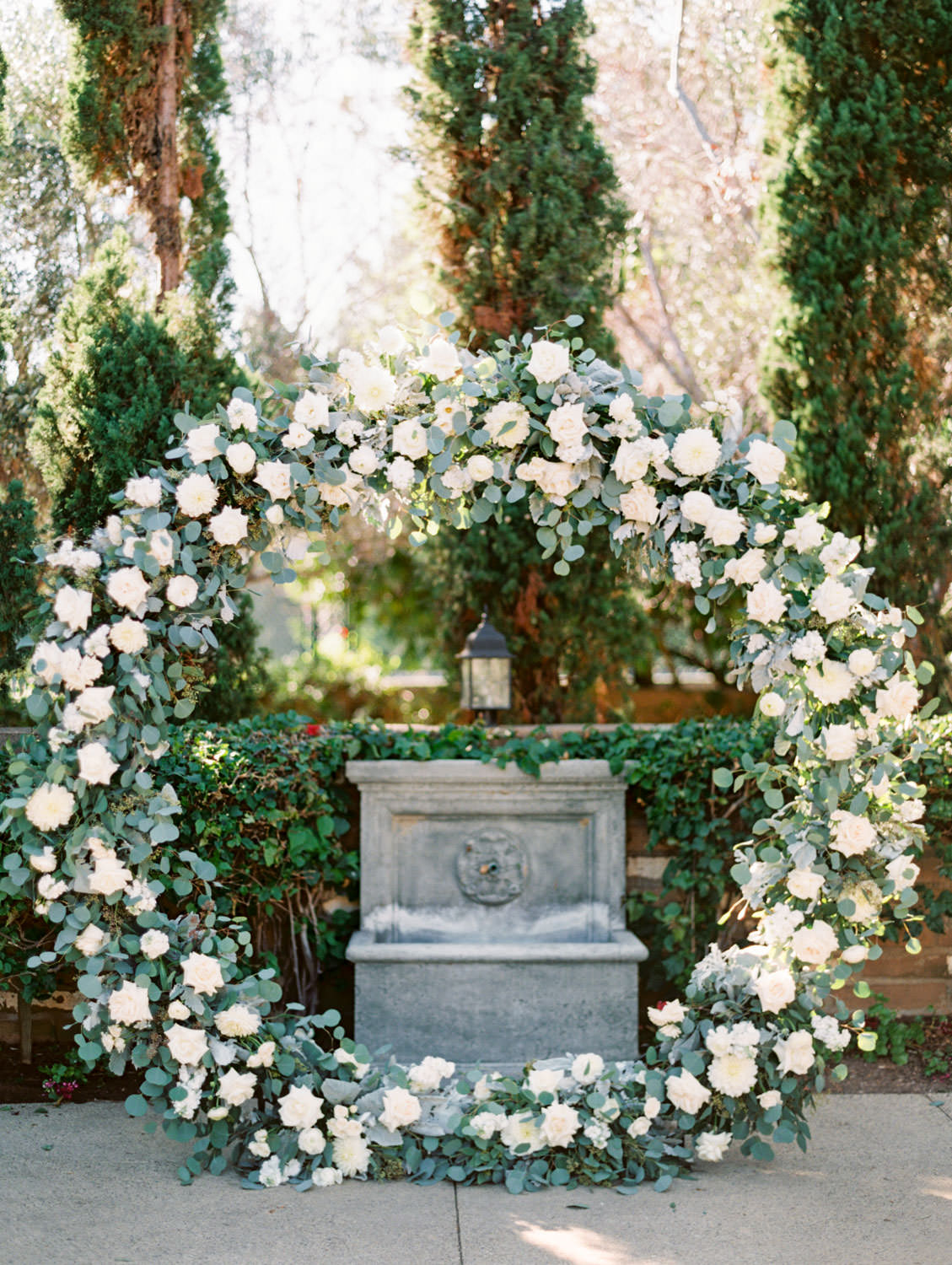 Circular ceremony arch with silver dollar eucalyptus, white dahlias and roses in front of a well and cypress trees. Olive Lawn ceremony. Estancia La Jolla wedding shot on film by Cavin Elizabeth Photography