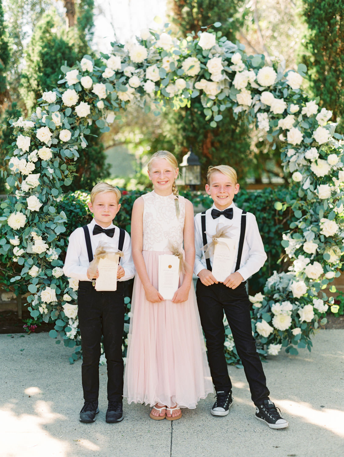 Child attendants holding ceremony programs in front of a circular ceremony arch with silver dollar eucalyptus, white dahlias and roses in front of a well and cypress trees. Olive Lawn ceremony. Estancia La Jolla wedding shot on film by Cavin Elizabeth Photography