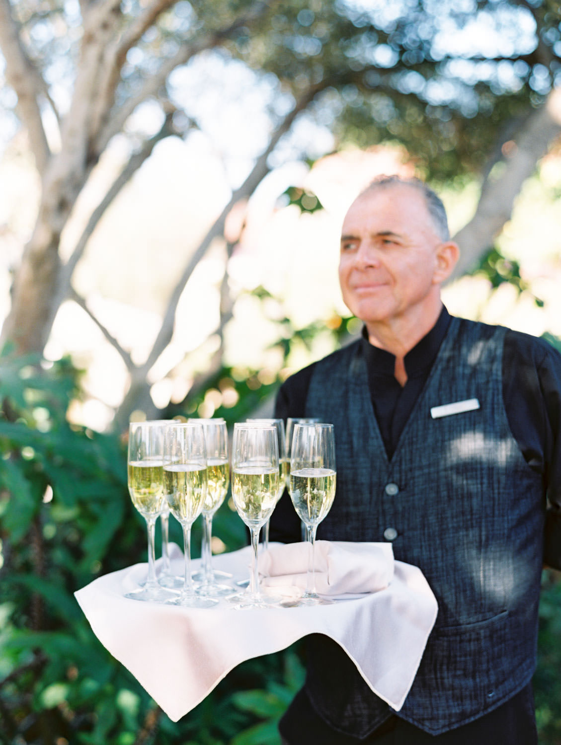 Tray pass champagne glasses before the ceremony. La Jolla wedding shot on film by Cavin Elizabeth Photography