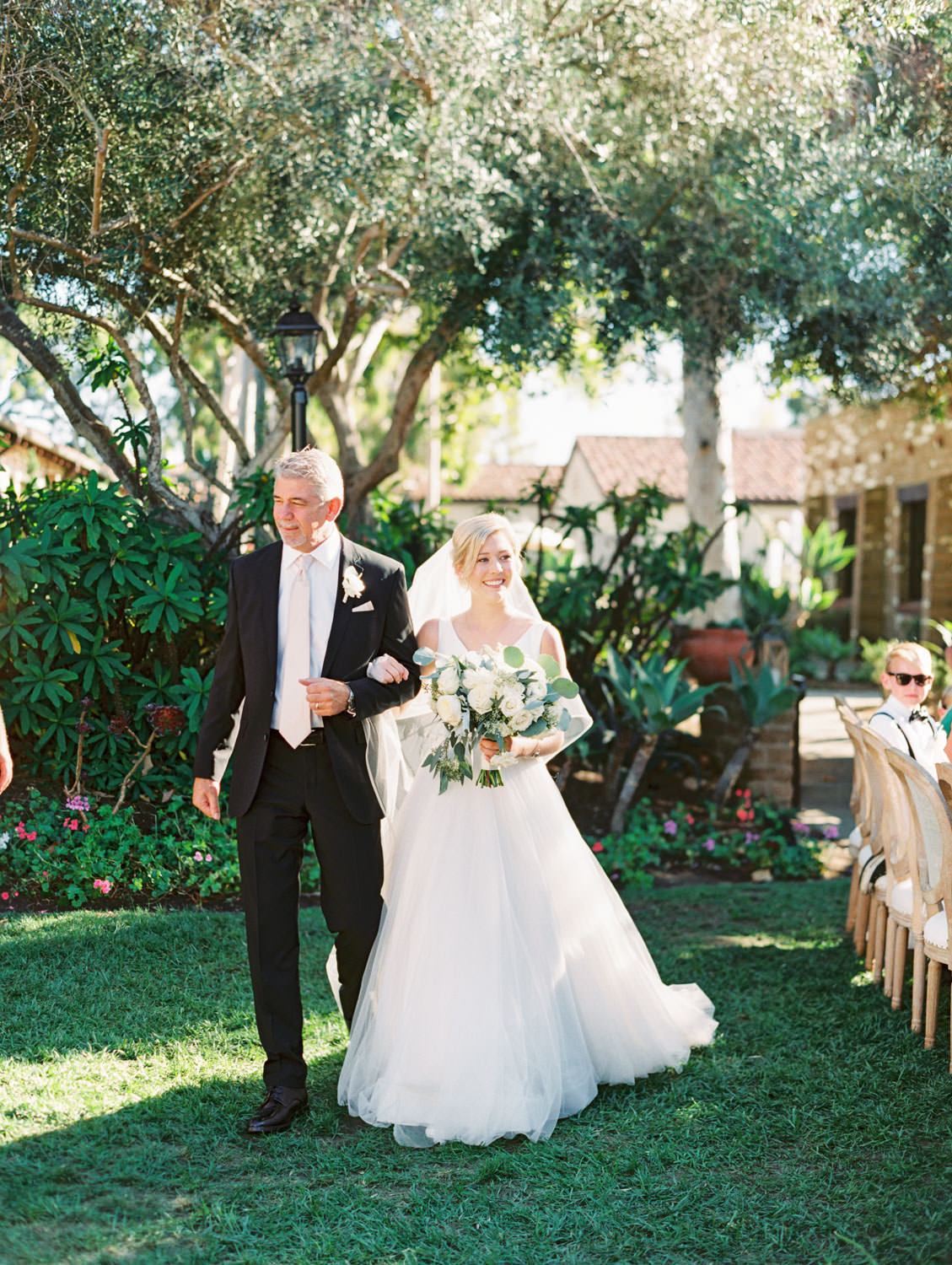 Father walking the bride down the aisle with bridal bouquet of eucalyptus, white dahlias and roses. Olive Lawn ceremony wedding shot on film by Cavin Elizabeth Photography
