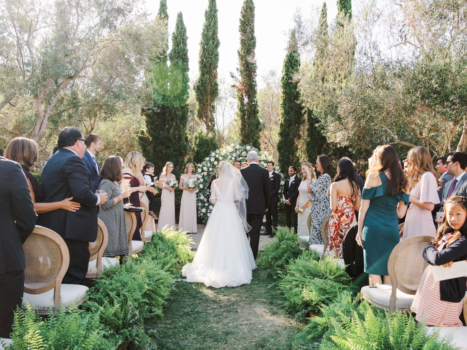 Circular ceremony arch with silver dollar eucalyptus, white dahlias and roses. Olive Lawn ceremony with cane back Louis chairs and ferns along the aisle. Estancia La Jolla wedding shot by Cavin Elizabeth Photography