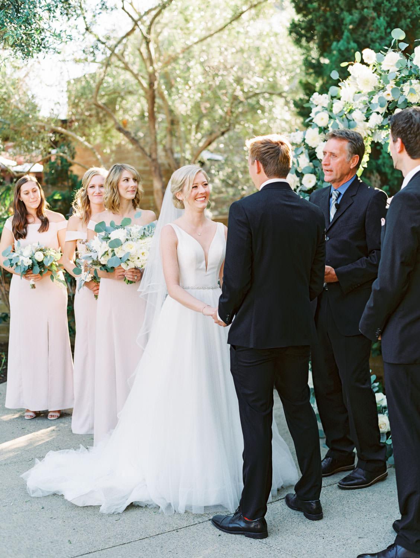Bride smiling during ceremony. Circular ceremony arch with silver dollar eucalyptus, white dahlias and roses. Estancia La Jolla wedding shot on film by Cavin Elizabeth Photography