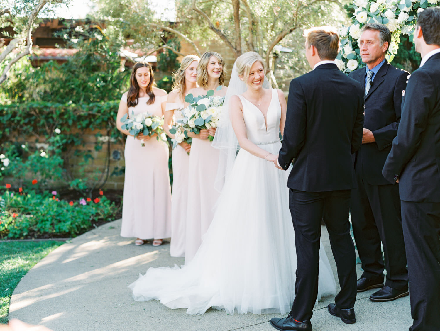 Bride smiling during ceremony. Circular ceremony arch with silver dollar eucalyptus, white dahlias and roses. Estancia La Jolla wedding shot on film by Cavin Elizabeth Photography
