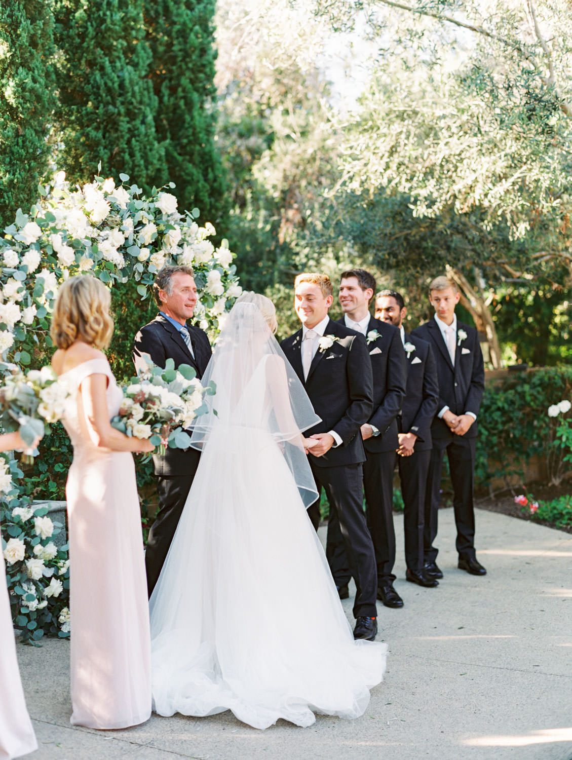Groom smiling during ceremony. Circular ceremony arch with silver dollar eucalyptus, white dahlias and roses. Estancia La Jolla wedding shot on film by Cavin Elizabeth Photography