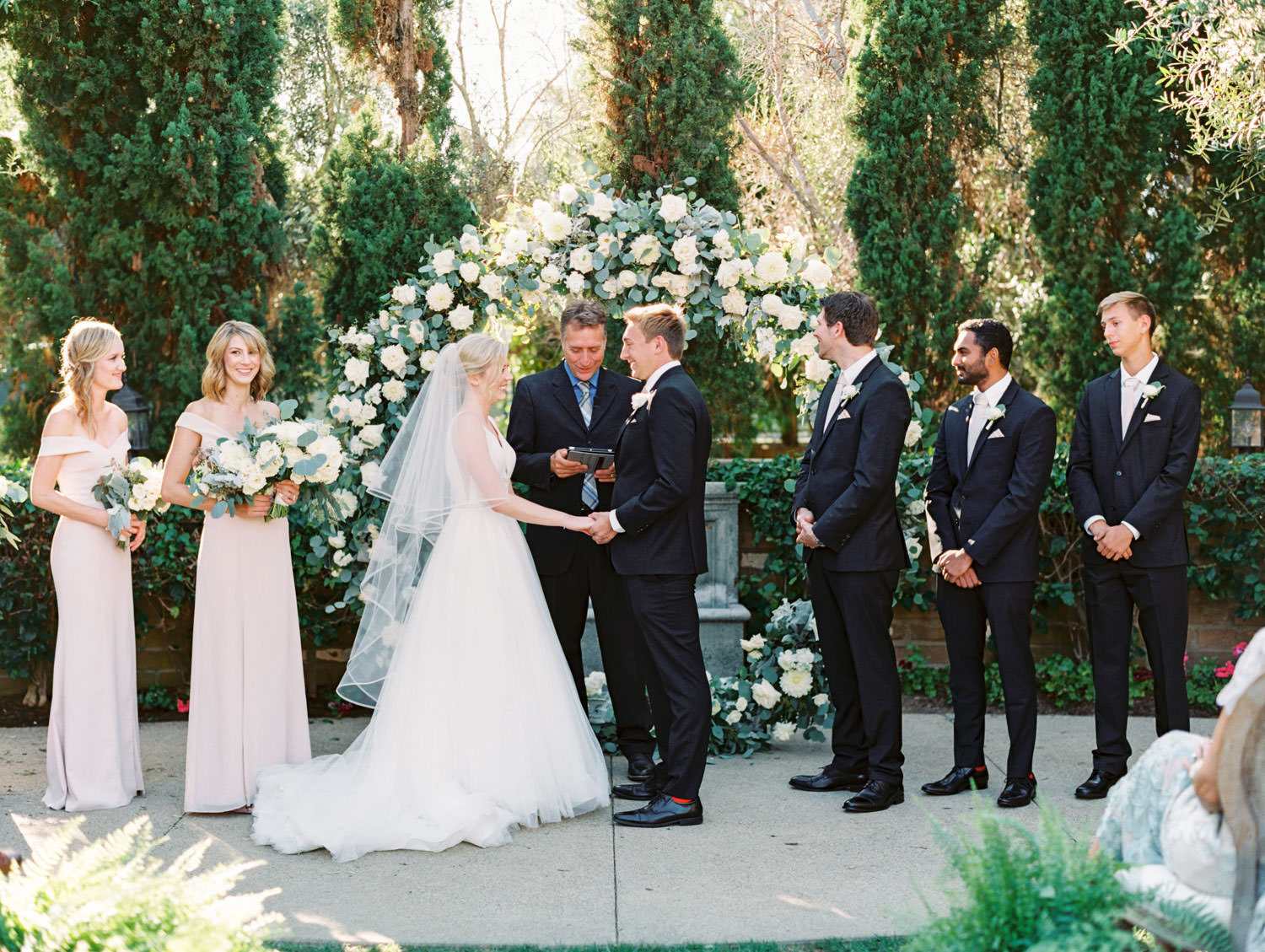 Bride and groom smiling at each other during ceremony. Circular ceremony arch with silver dollar eucalyptus, white dahlias and roses. Estancia La Jolla wedding shot on film by Cavin Elizabeth Photography